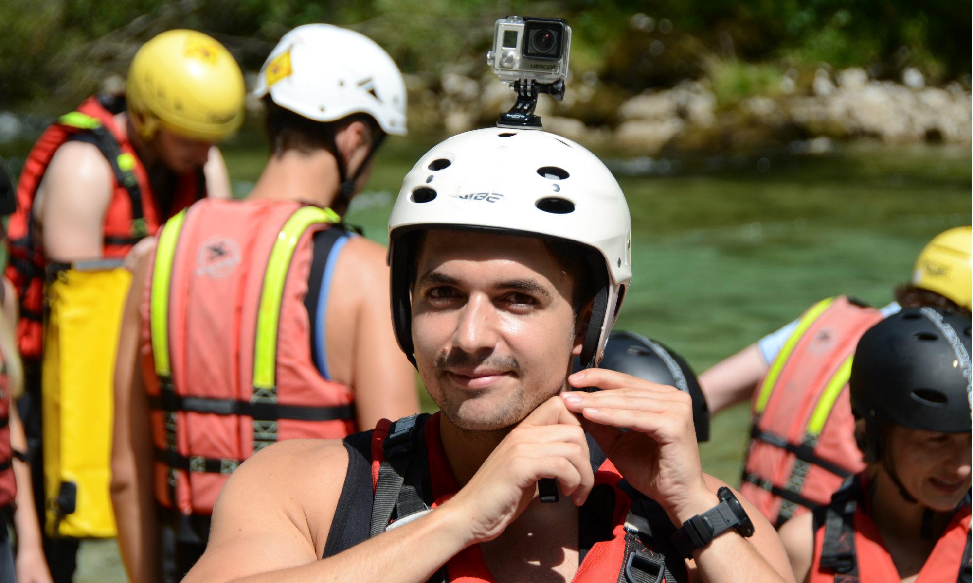 Ein Teilnehmer einer Rafting Tour schließt den Verschluss seines Helmes.