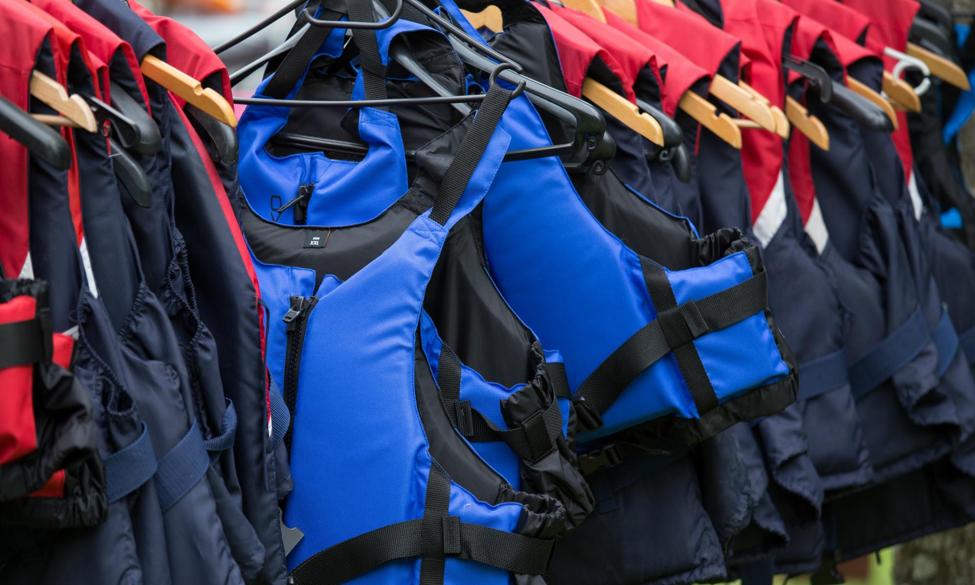 Schwimmwesten in unterschiedlichen Farben und Größen hängen auf einer Kleiderstange.
