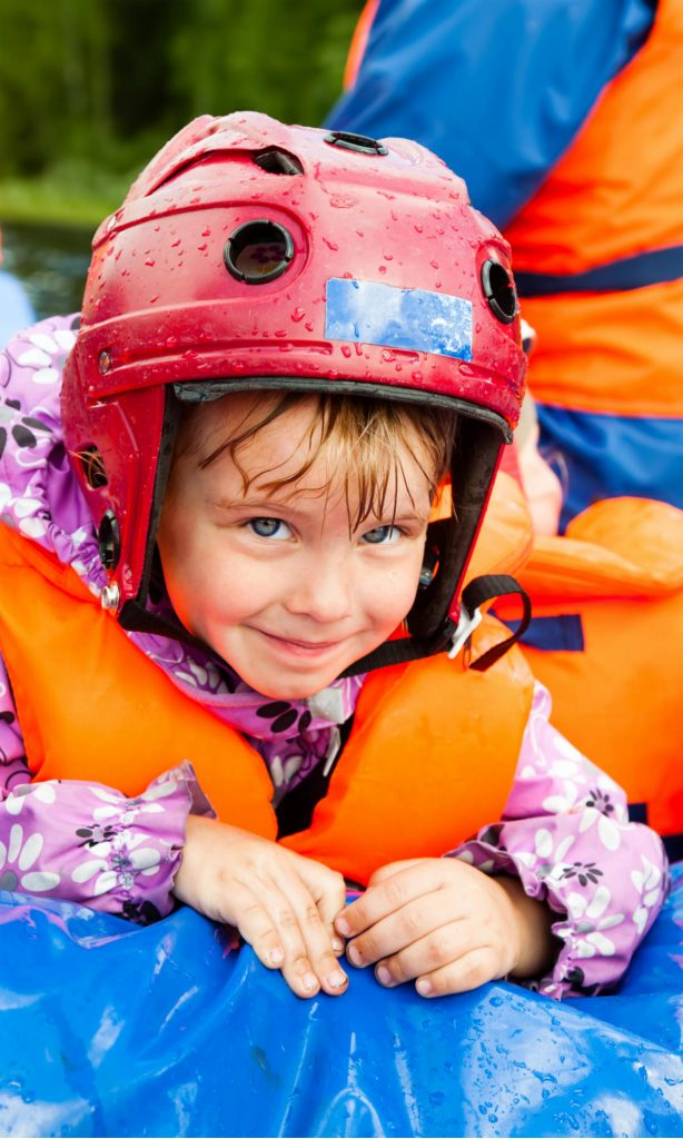 Ein kleines Mädchen sitzt mit Helm und Schwimmweste bekleidet in einem Schlauchboot und hält sich am Rand fest.