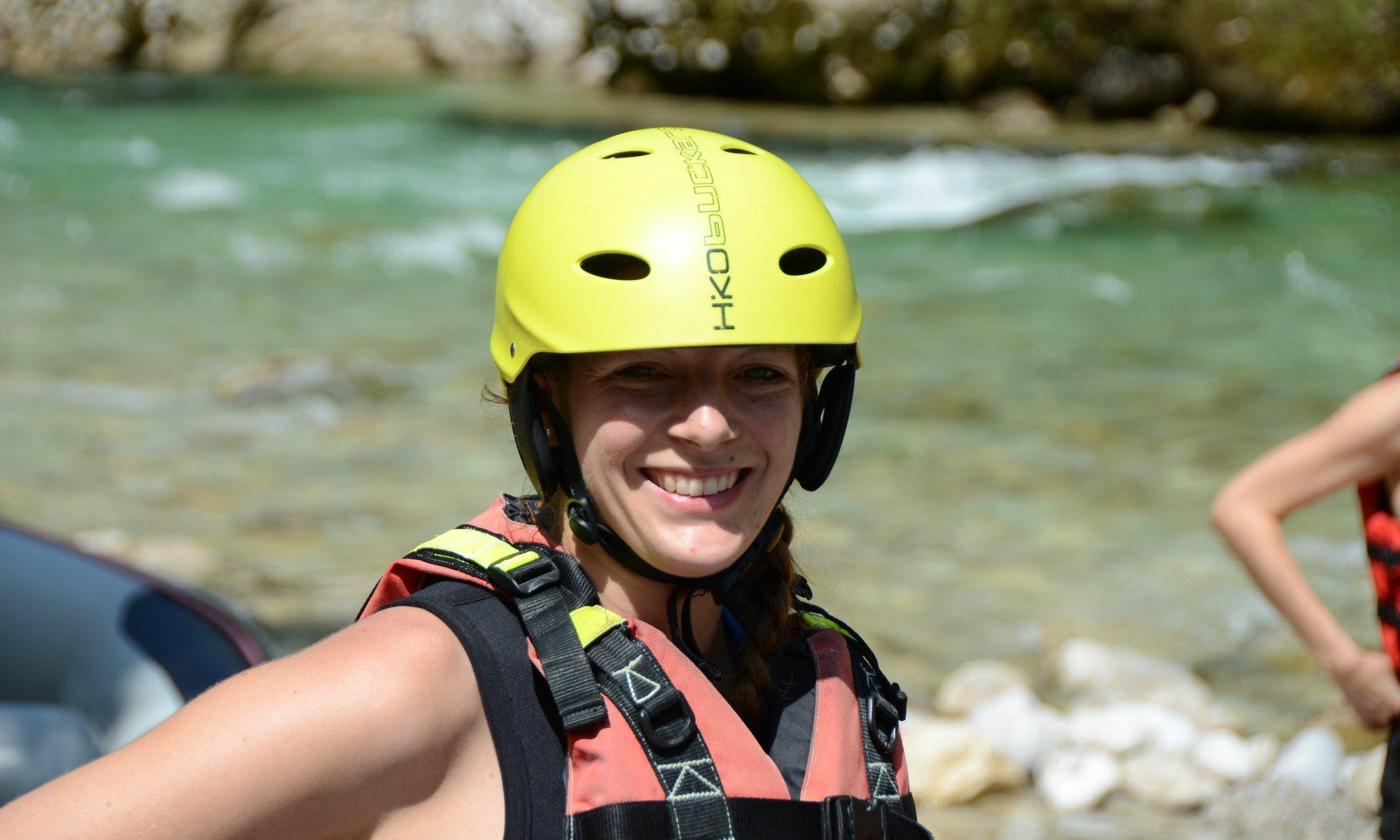 Eine Rafterin in Schwimmweste und mit Helm wartet auf ihre erste Rafting Tour.