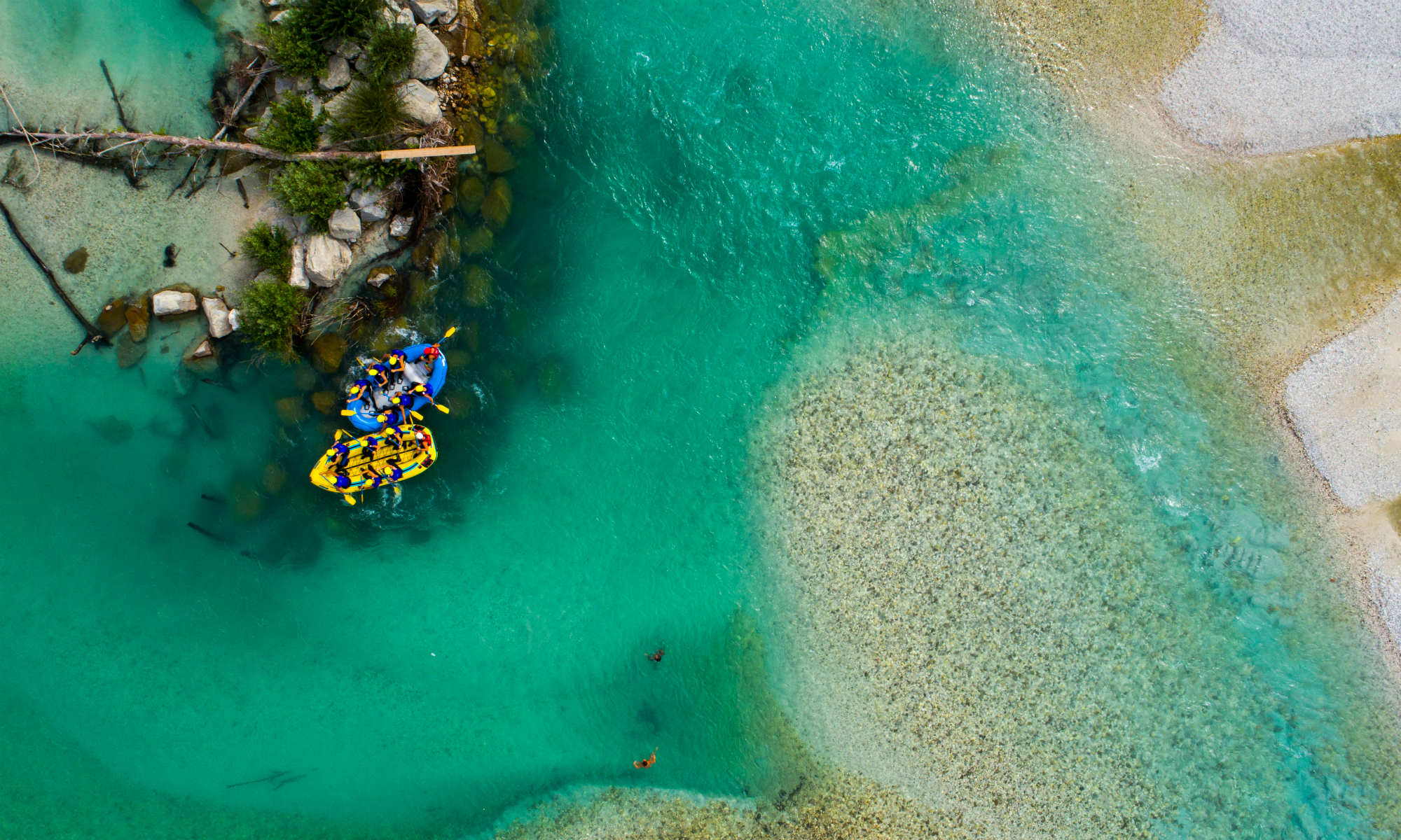 Zwei Schlauchboote auf einem smaragdgrünen Fluss von oben betrachtet.