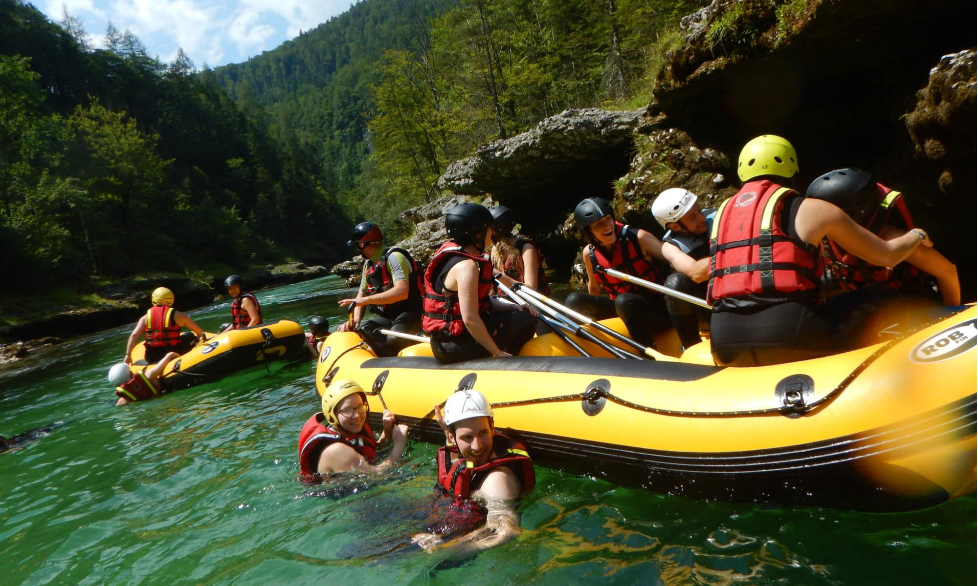 Bei einer Rafting Tour im Gesäuse lassen sich einige Teilnehmer neben dem Raft im Wasser treiben.