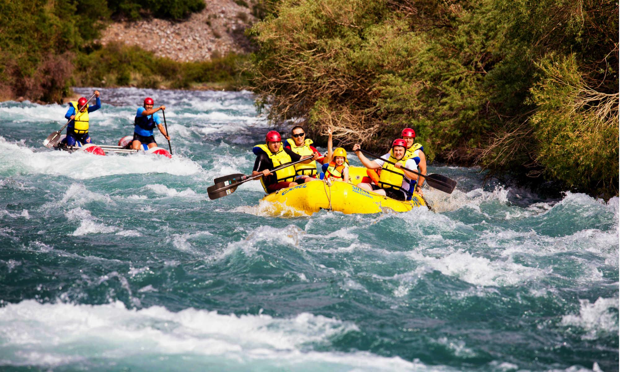 Mehrere Personen unterschiedlichen Alters sitzen in 2 Schlauchbooten und paddeln bei einer Rafting Tour auf einem Fluss.
