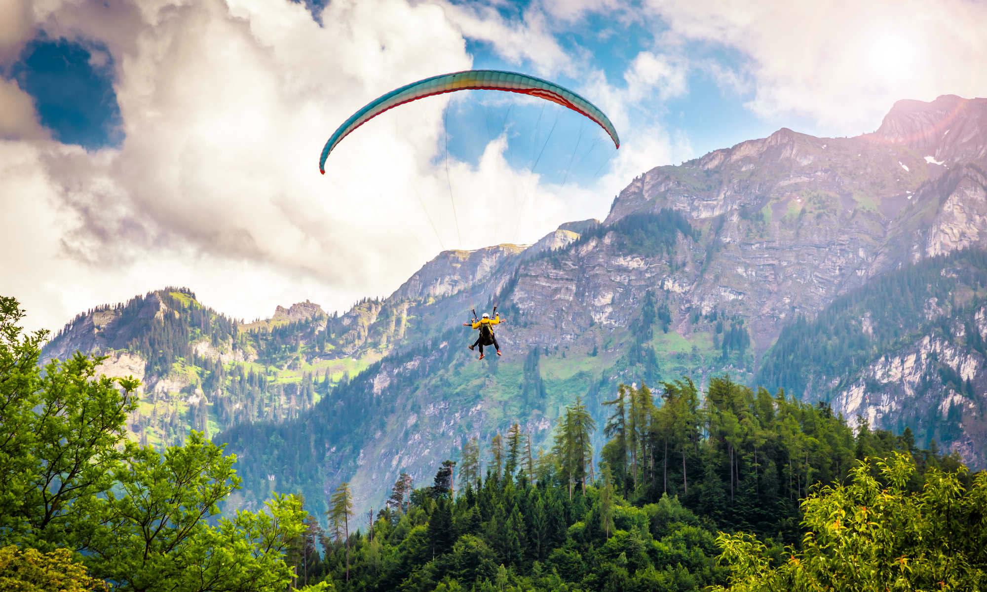 Ein Paraglider gleitet vor der Bergkulisse in Interlaken durch die Lüfte.