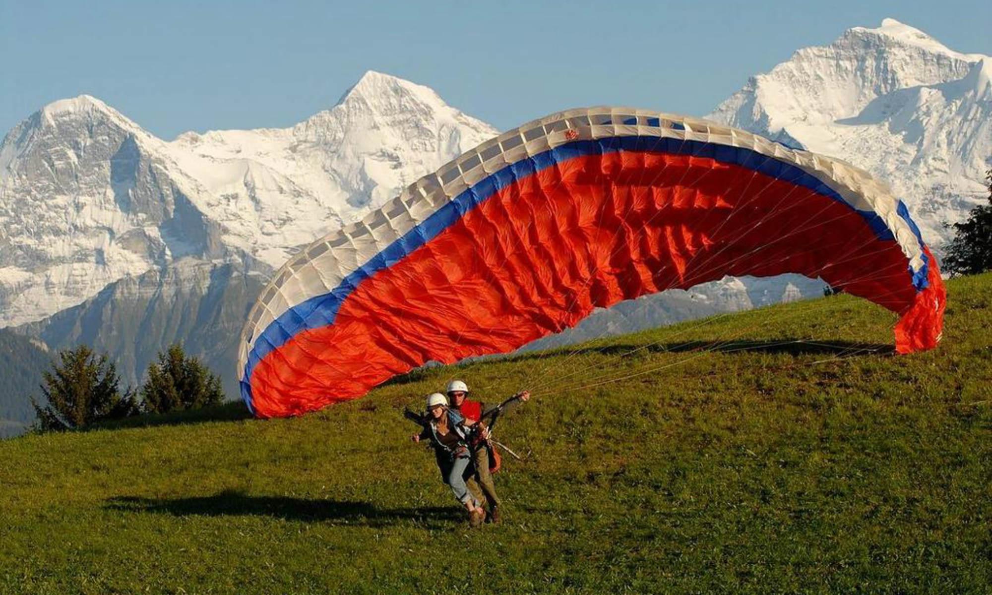 2 Tandem Paraglider beim Start ihres Fluges vor dem Jungfraumassiv.