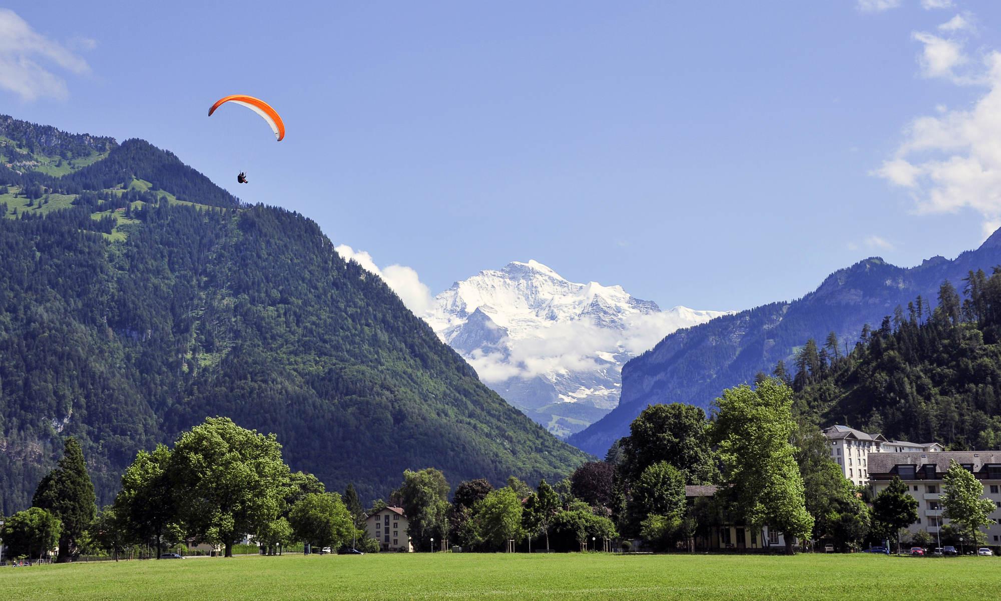 Ein Paraglider vor dem schneebedeckten Berg Jungfrau im schweizerischen Kanton Bern.
