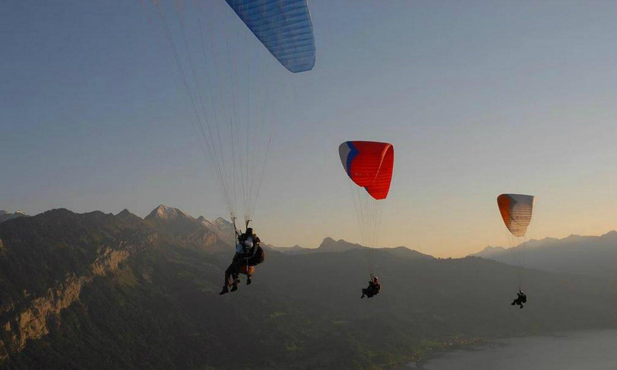 Mehrer Paraglider segeln bei Sonnenaufgang über die Berglandschaft in Interlaken.