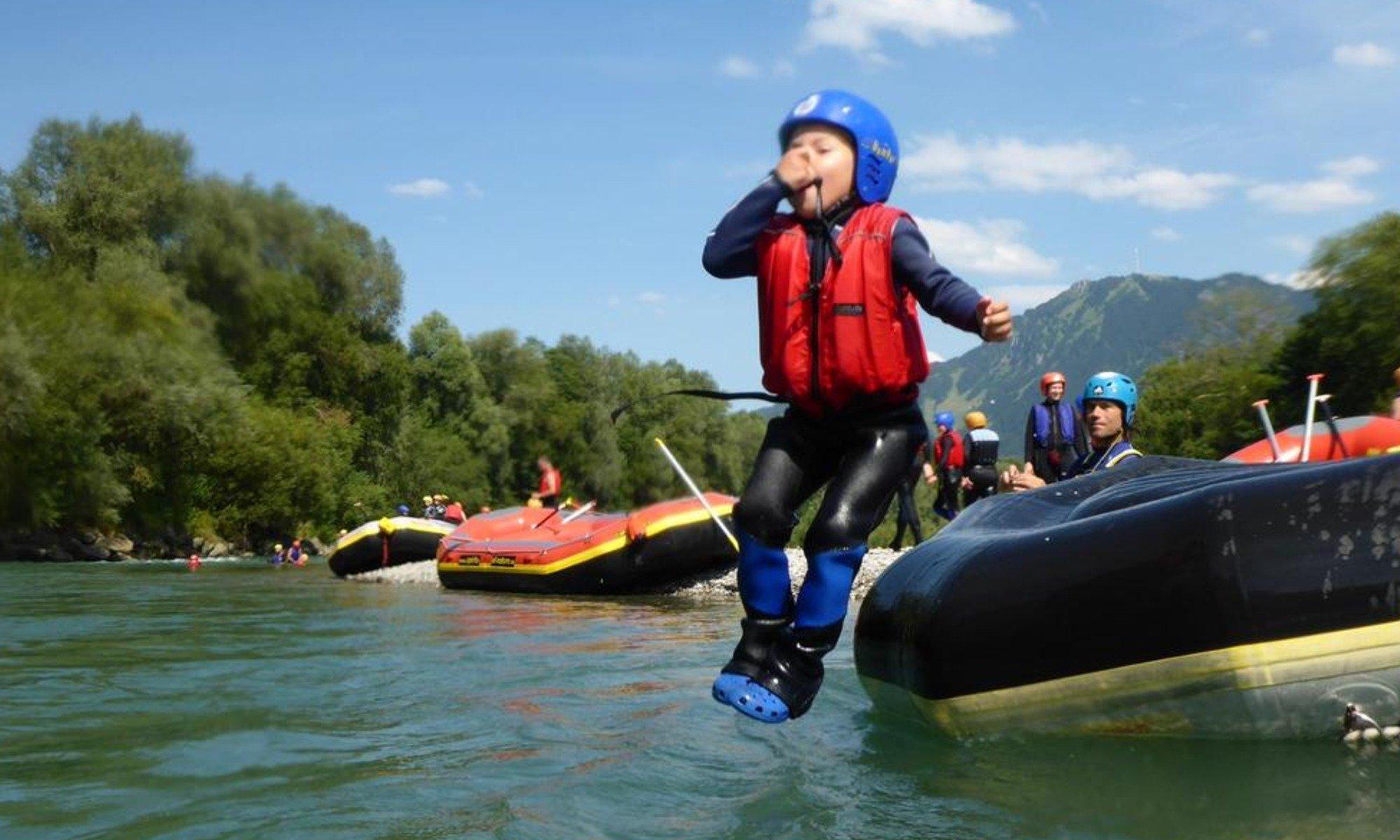 Ein Kind springt beim Rafting im Allgäu von einem Schlauchboot in die Iller.