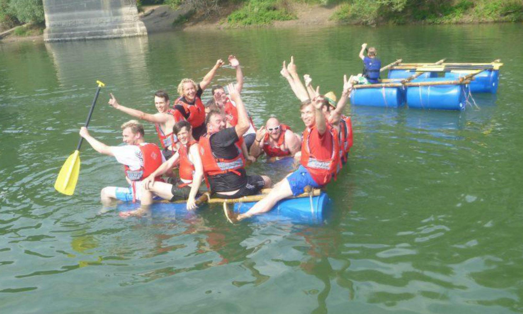 Eine Gruppe auf einem selbstgebauten Floß beim Rafting in NRW.