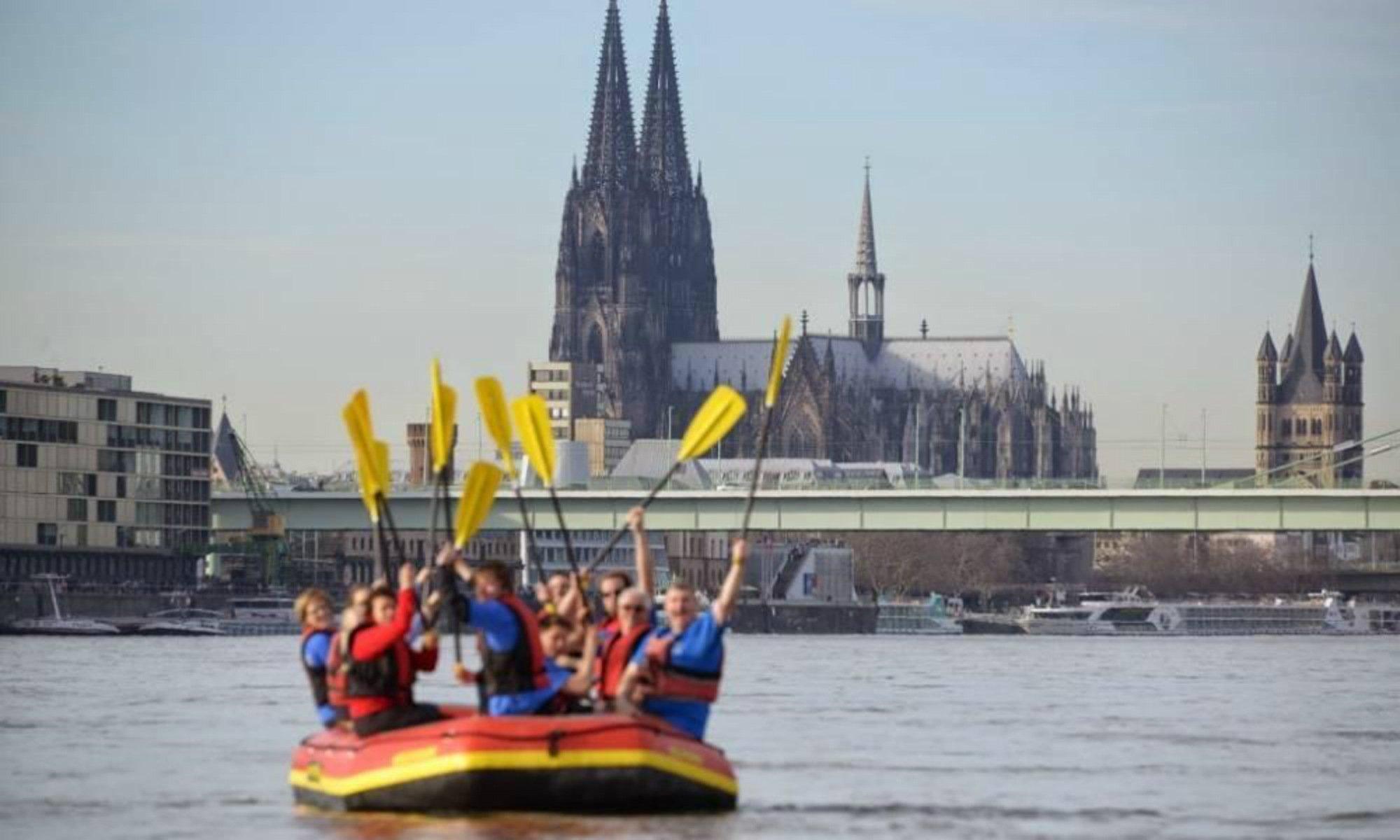 Eine Gruppe sitzt beim Rafting in NRW in einem Schlauchboot vor der Skyline von Köln.