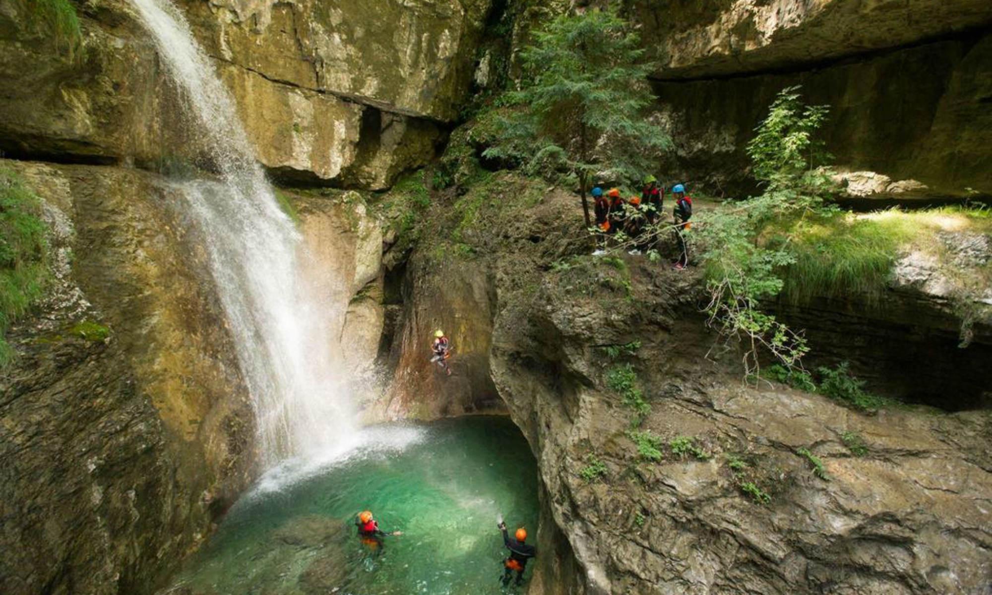 Eine Gruppe springt beim Canyoning am Gardasee in der Schlucht des Rio Neros von einem Felsen in ein Wasserbecken.