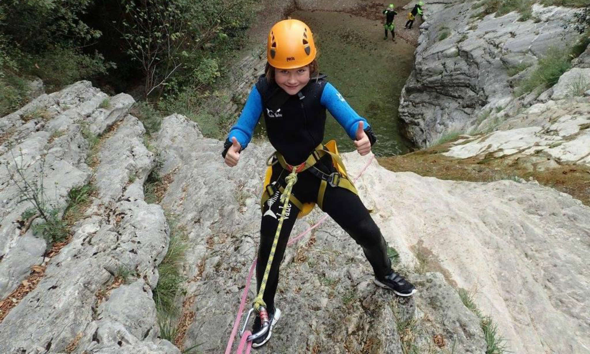 Ein Kind seilt sich an einer Wand in der San Michele Schlucht beim Canyoning am Gardasee ab.
