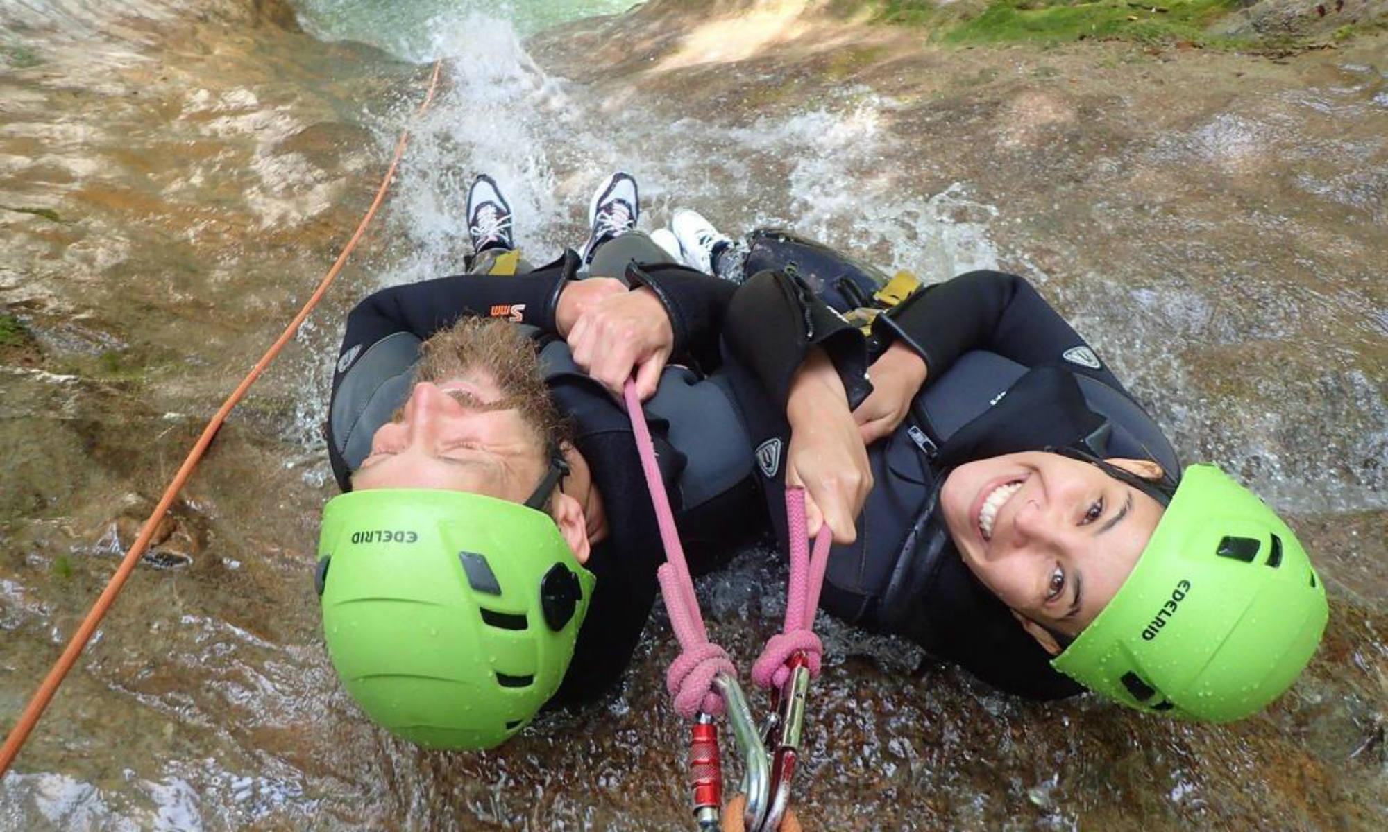 Zwei Personen seilen sich beim Canyoning am Gardasee in der Schlucht Vione an einem Wasserfall ab.