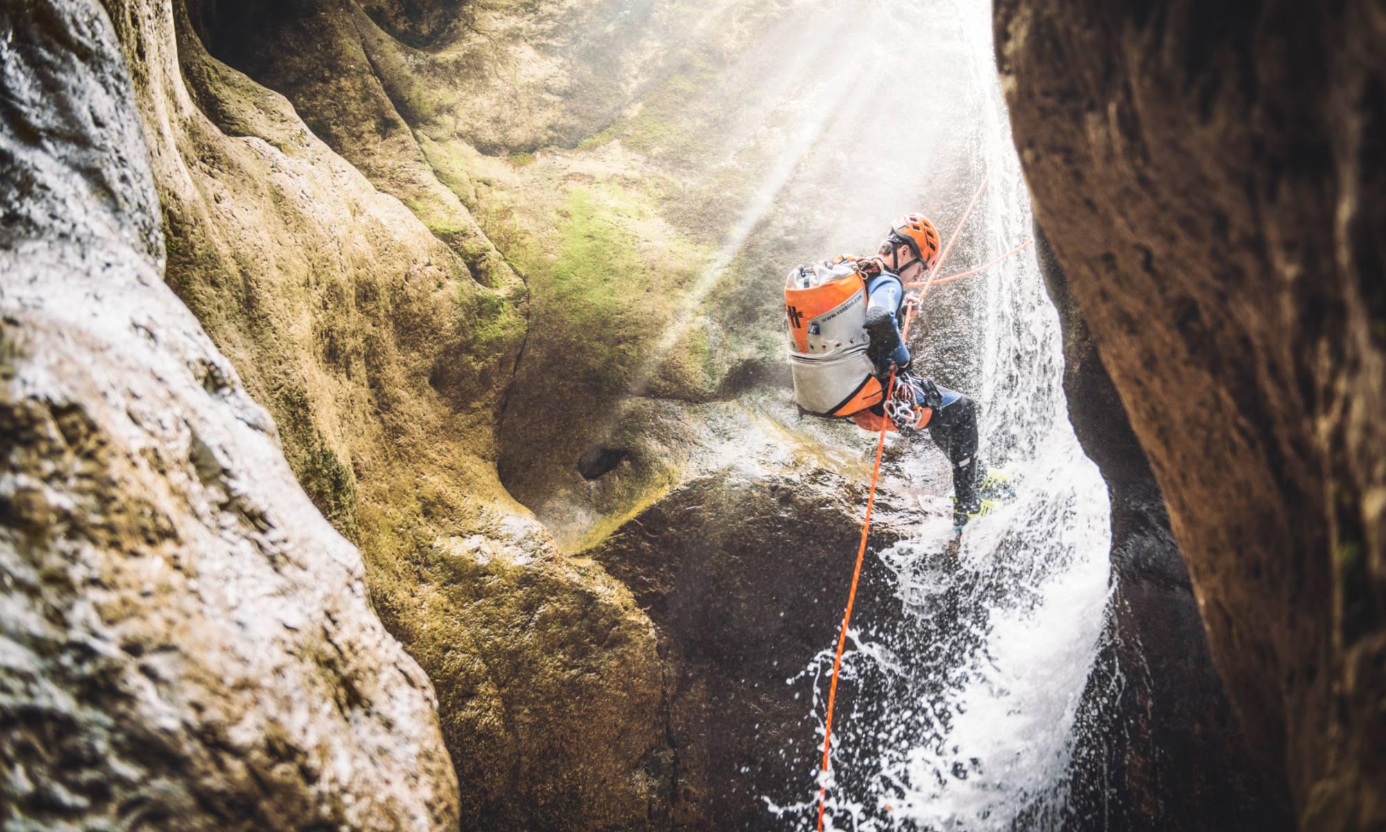 Ein Mann seilt sich beim Canyoning in der Steiermark in Palfau an einem kleinen Wasserfall ab.