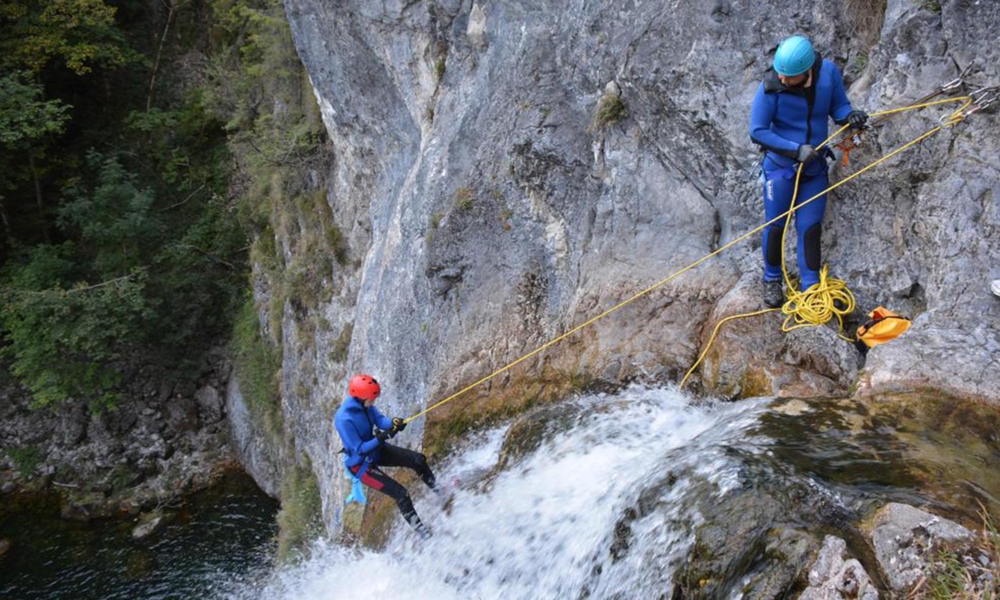 Zwei Canyoner seilen sich beim Canyoning in der Steiermark an einem Wasserfall ab.