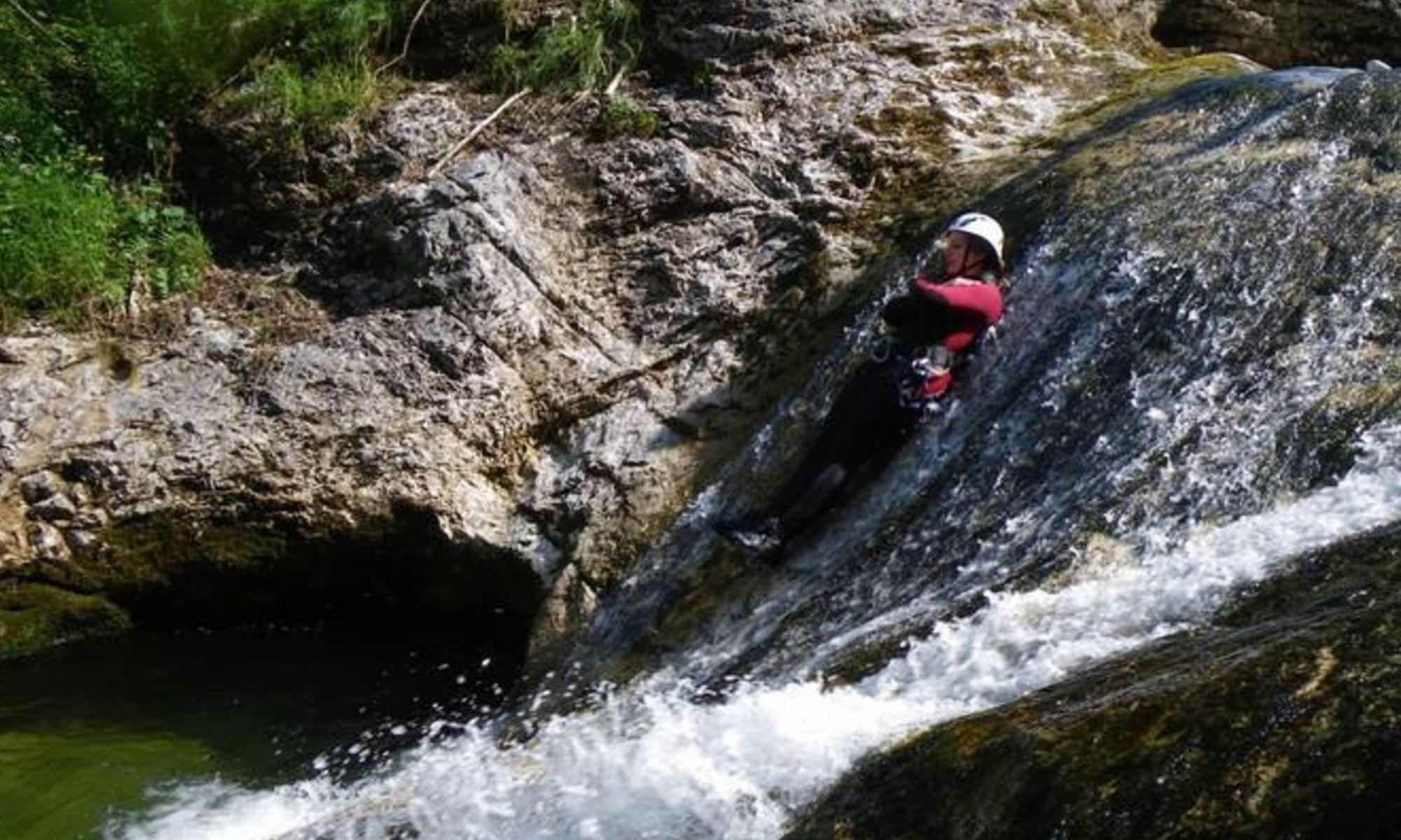 Eine Teilnehmerin einer Canyoning Tour in Wildalpen rutscht an einem Wasserfall hinab.