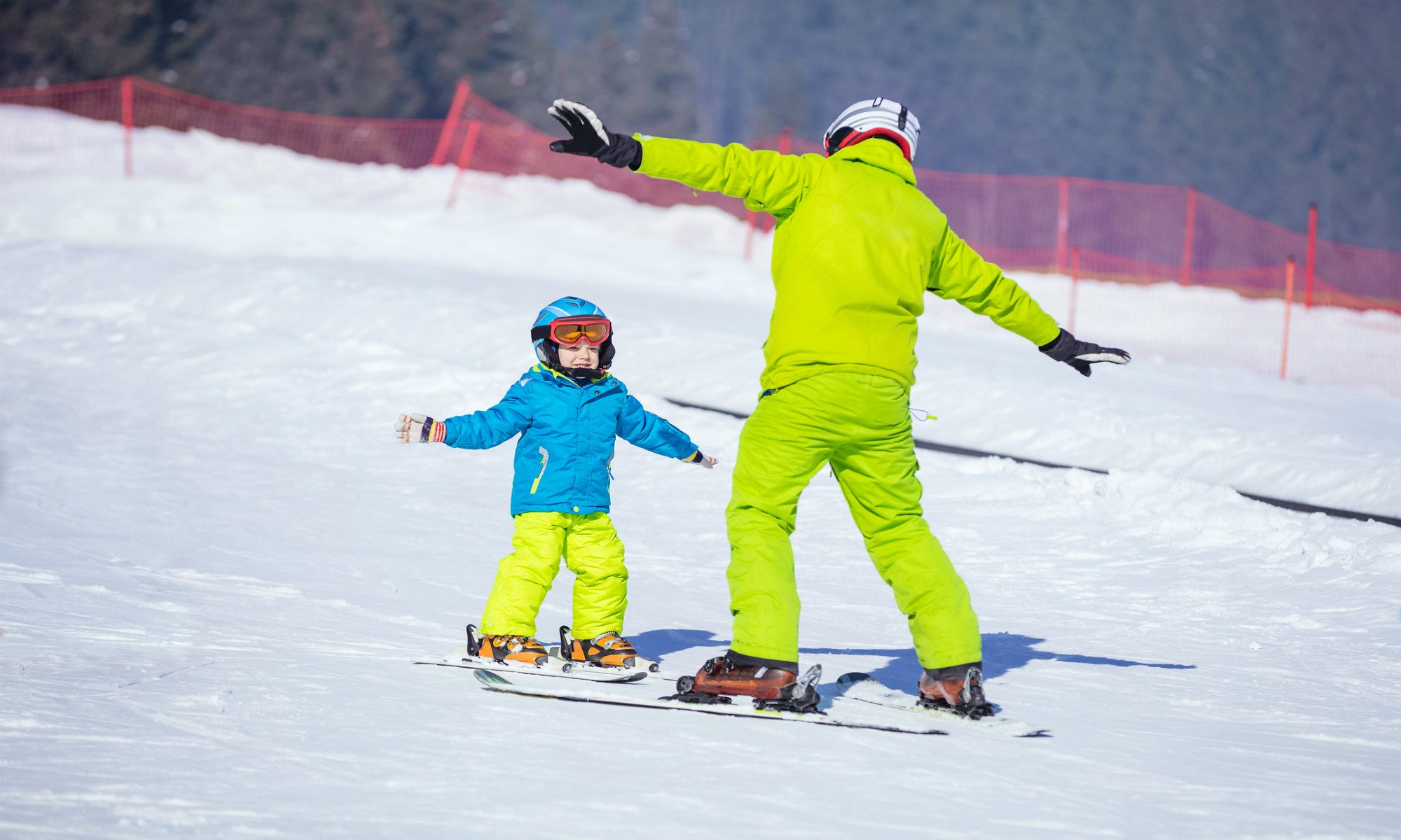 Een klein jongetje doet oefeningen met zijn skileraar op de oefenpiste.