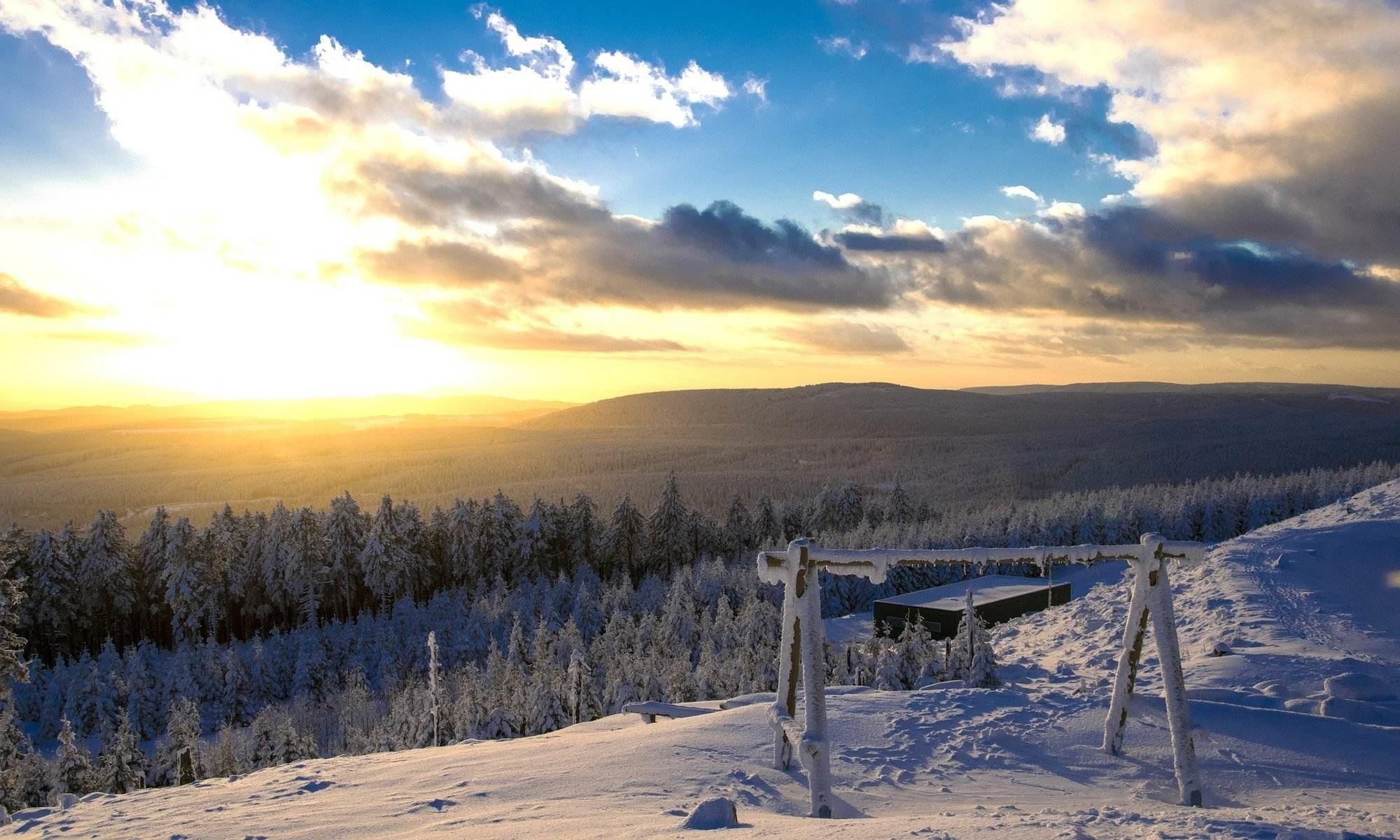 De zon gaat onder boven de witte piste van Braunlage.