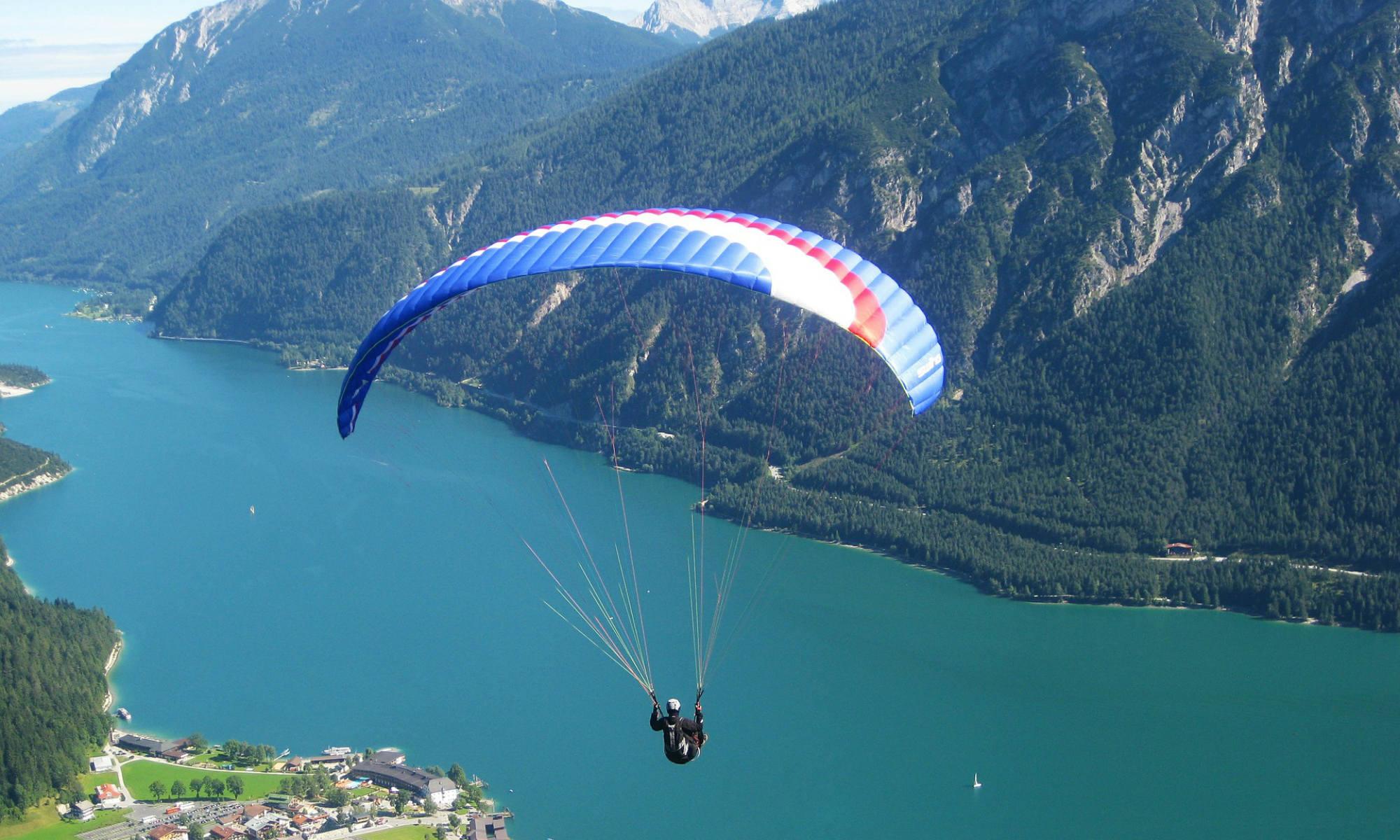 Ein Gleitschirmflieger über dem Achensee, mit den Alpen im Hintergrund.