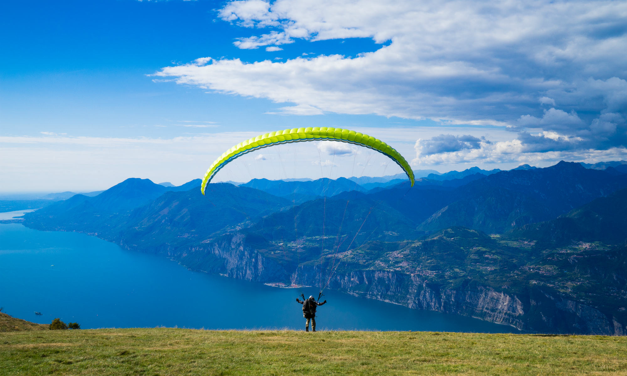 Ein Paraglider vor dem marineblauen Gardasee und dem umliegenden Bergpanorama.