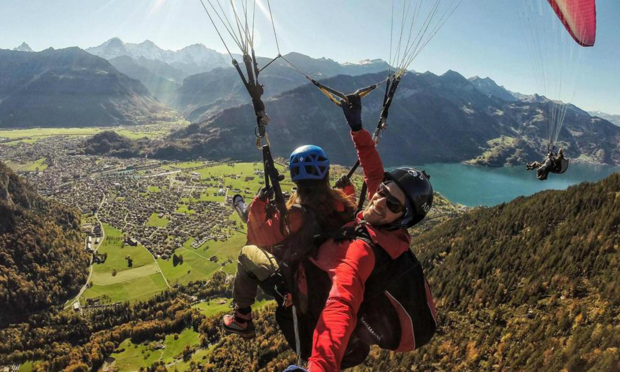 4 Paraglider fliegen vor dem Panorama der Berge und Seen in Interlaken.