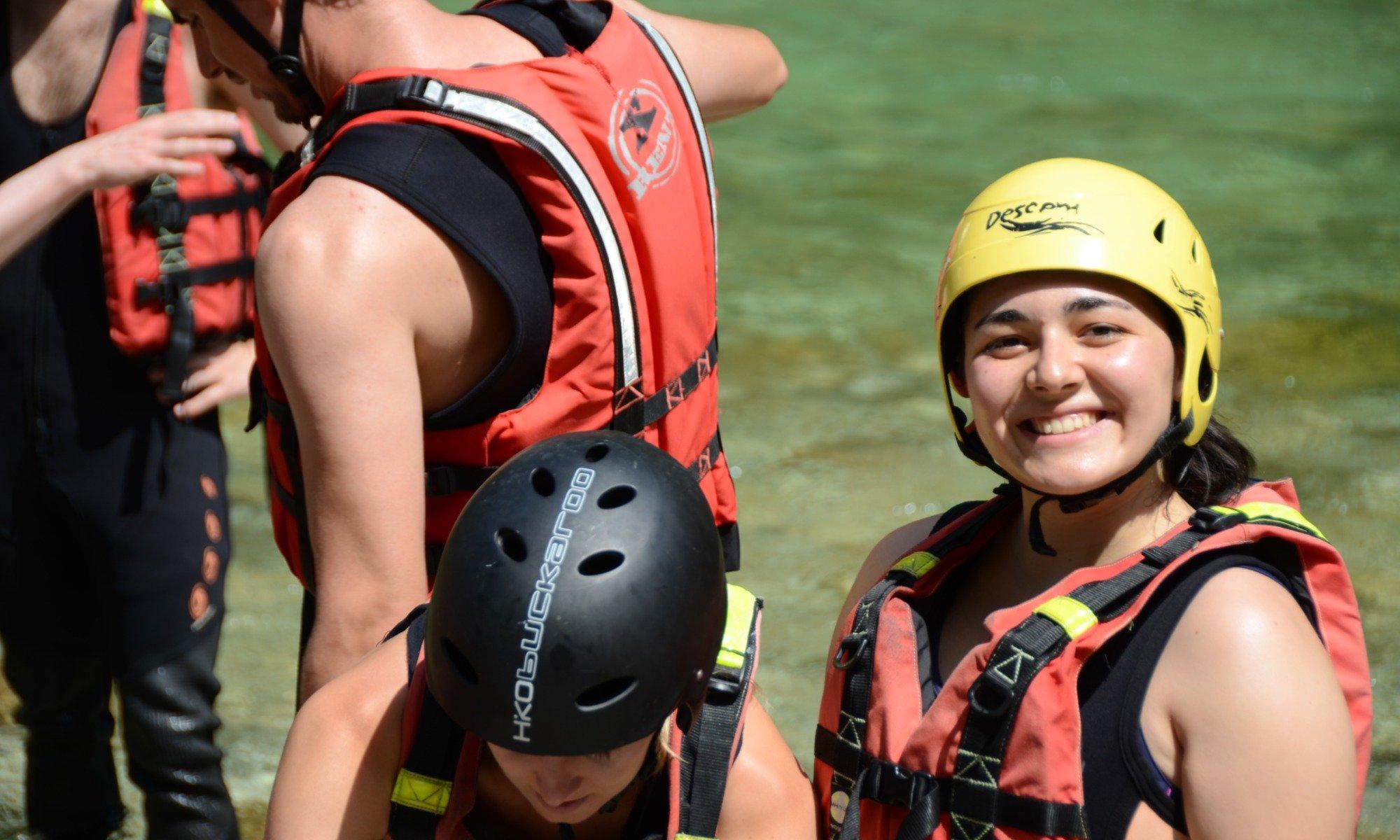Mehrere Personen bereiten sich beim Rafting im Allgäu auf ihre Tour vor.