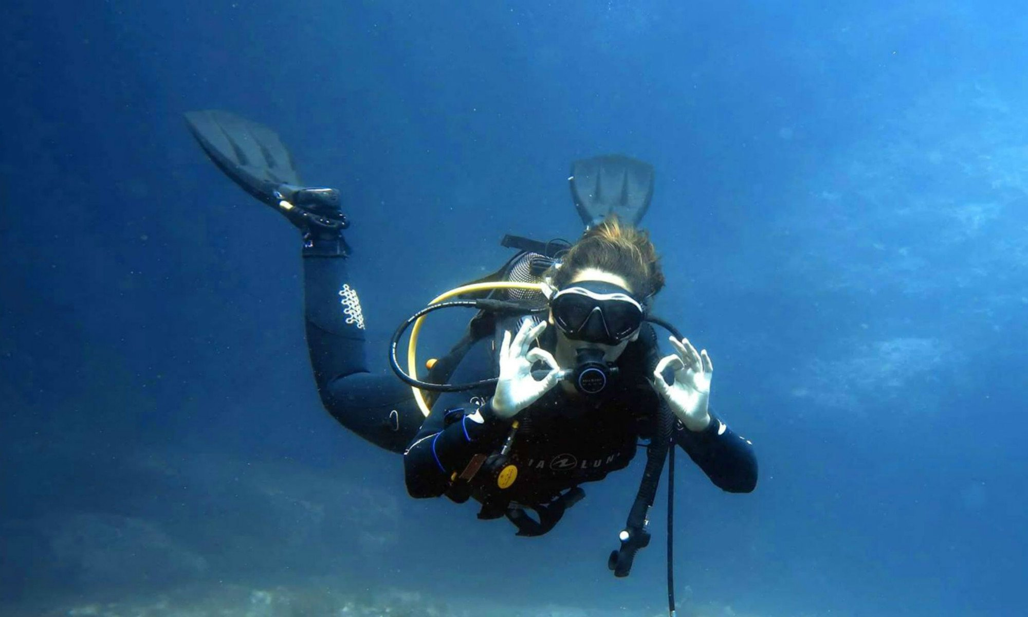 A female diver is signalling 'O.K.' while scuba diving in Malta.
