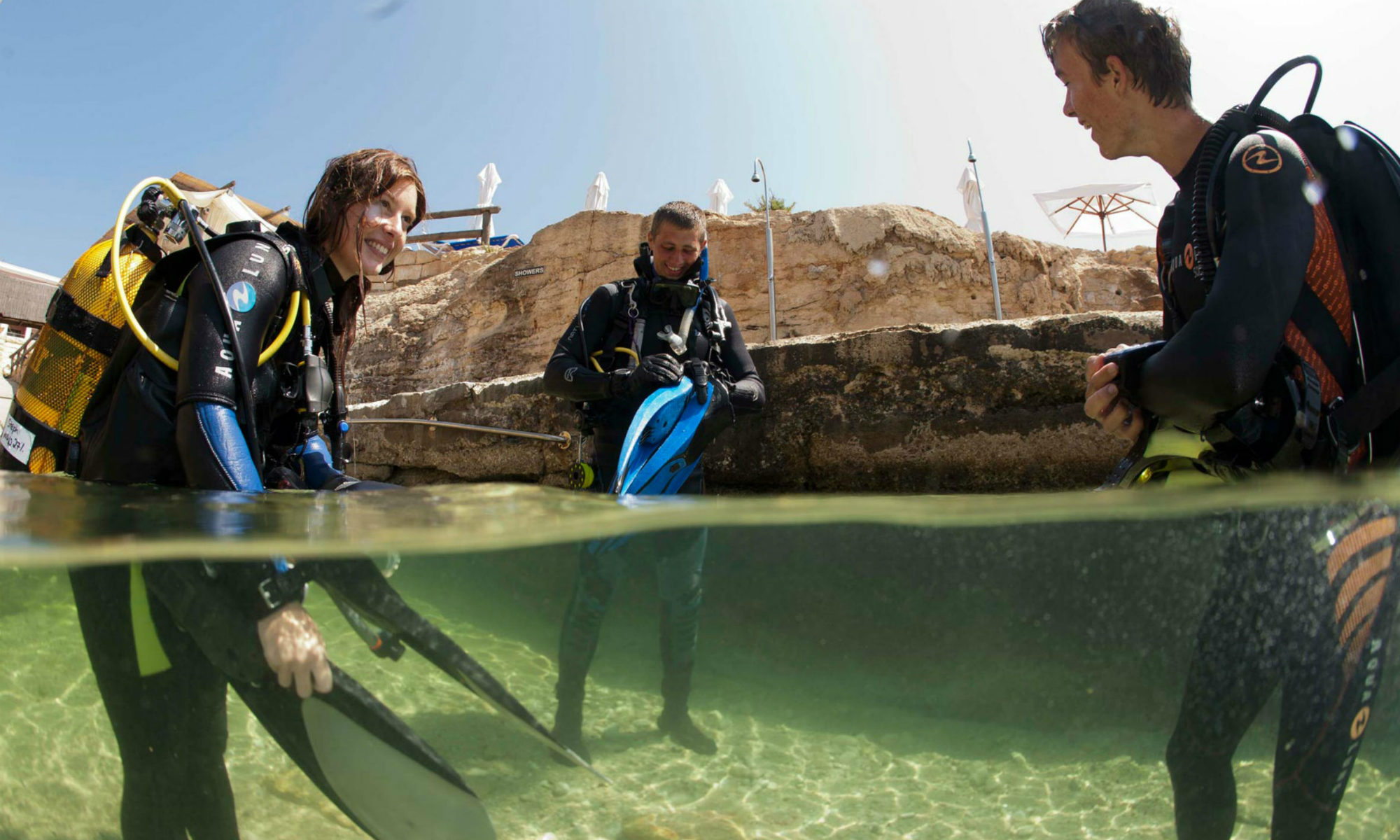A group of divers gearing up in shallow water, preparing to go scuba diving in Malta.