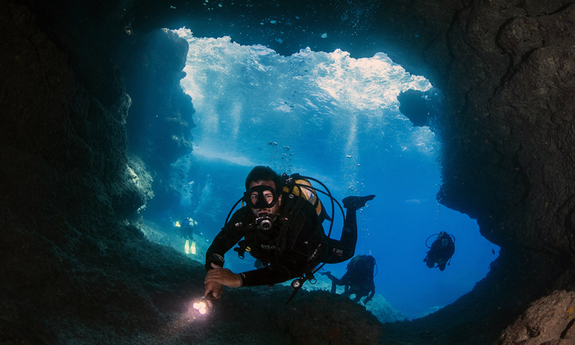 A group of divers is diving through the island of Comino's famous Santa Maria Caves.