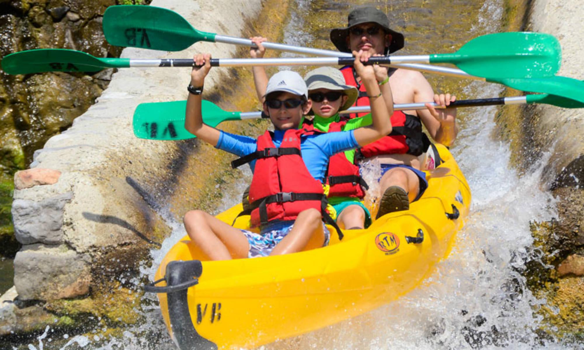 Deux enfants et leur père s'amusent lors d'une descente en canoë sur l'Ardèche.
