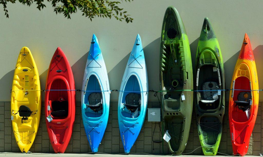 Des canoës et kayaks colorés alignés contre un mur.