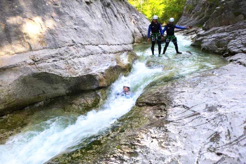 Lors de son activité canyoning dans le Verdon, une personne glisse dans un toboggan naturel dans le canyon du Haut Jabron sous les yeux de deux amis.