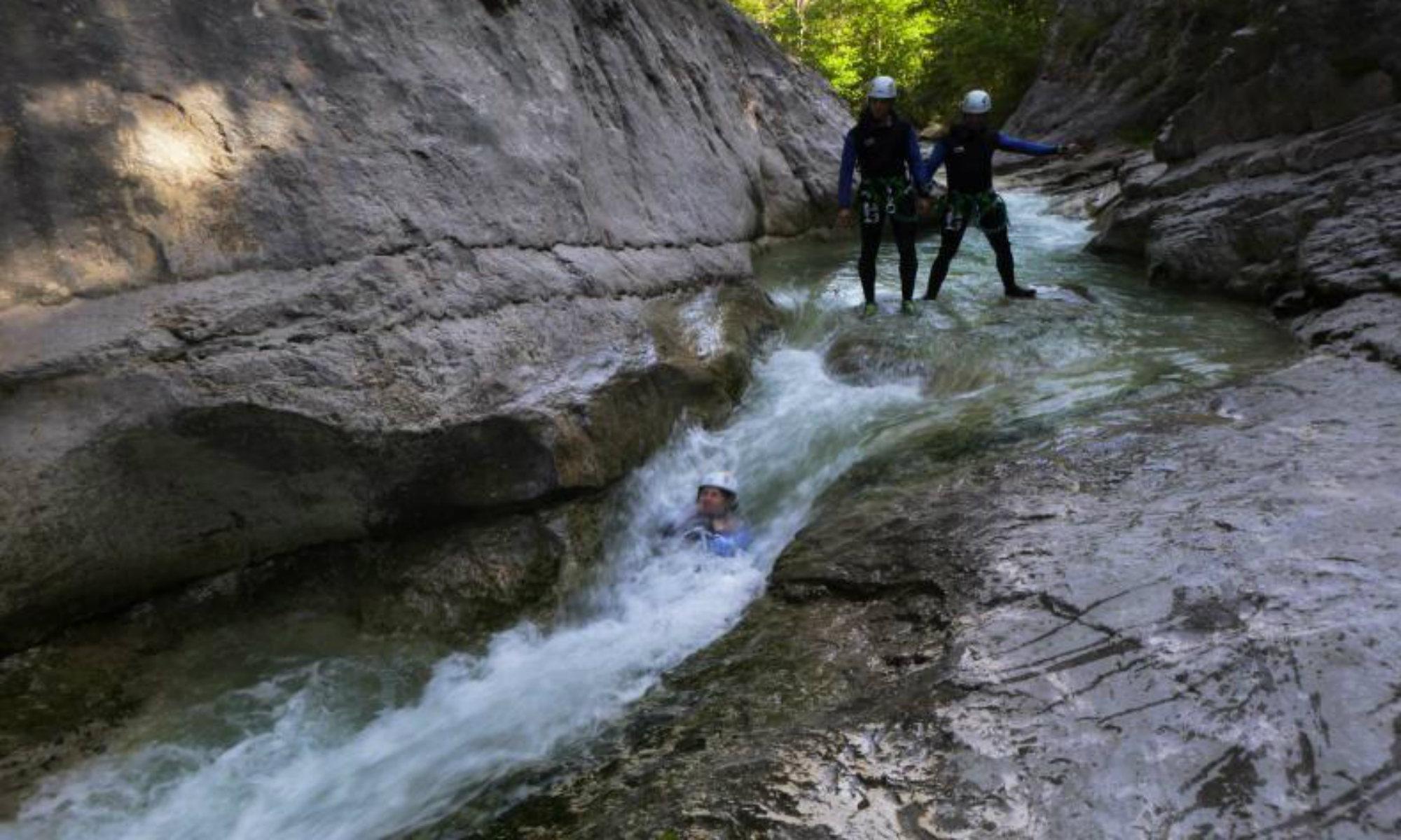 Une personne glisse dans un toboggan naturel dans le canyon du Haut Jabron sous les yeux de deux amis.
