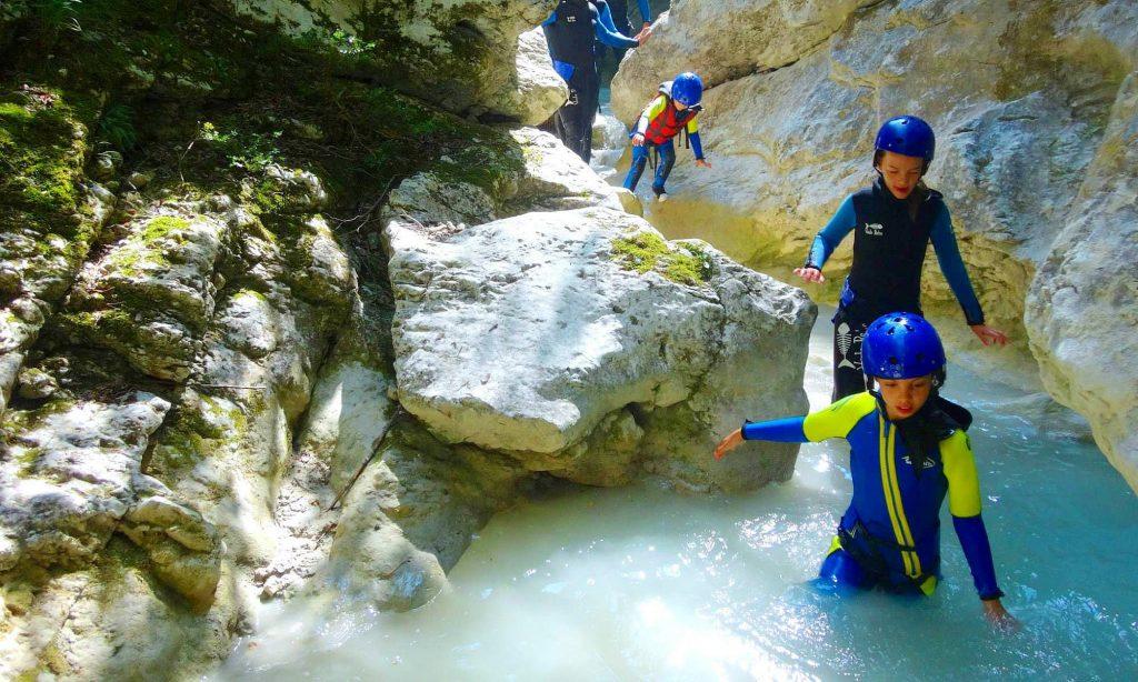 Lors d'une activité canyoning dans le Verdon, un groupe de canyonistes s'apprête à glisser dans un toboggan naturel.