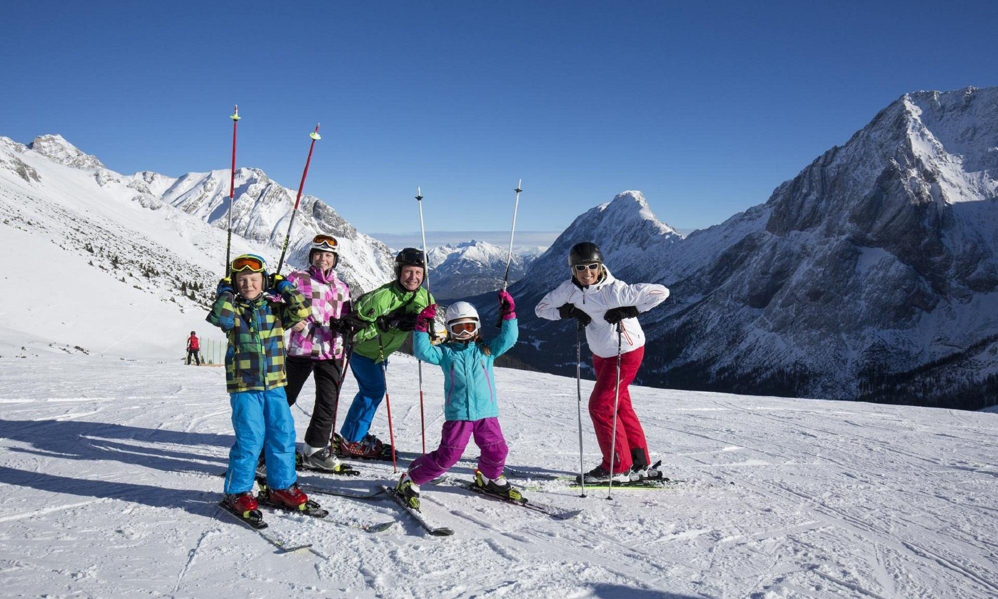 Een groepje skiërs heeft plezier op de piste.