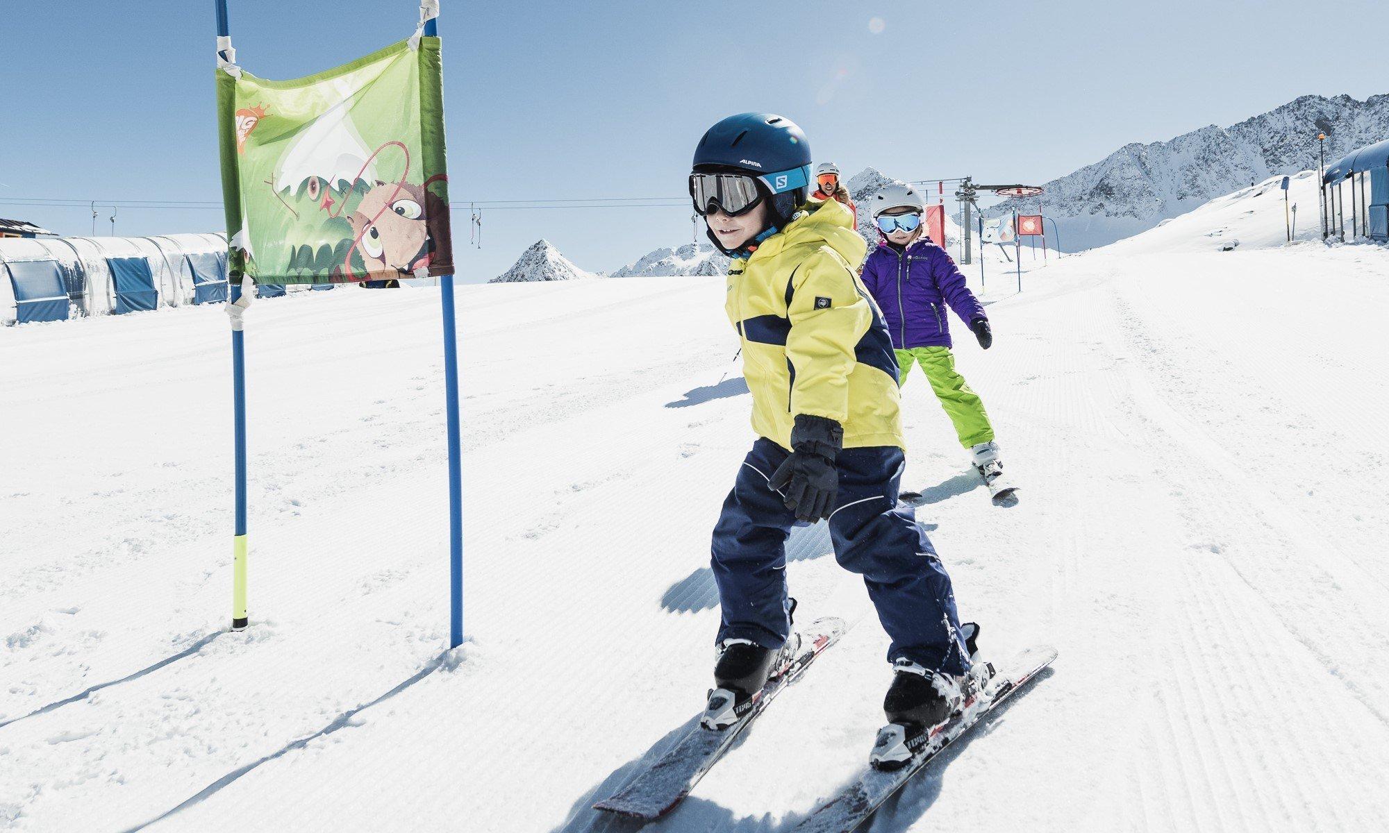 Kinderen leren skiën in het zonnige kindergebied