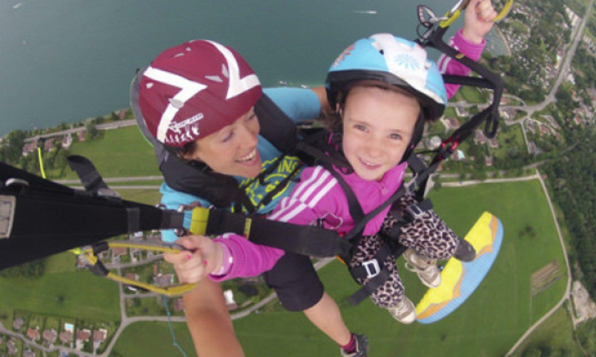 Une fillette tout sourire lors d'un vol en parapente à Annecy avec une femme pilote.