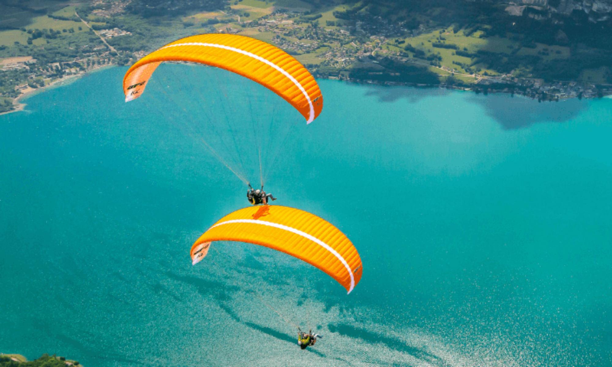 Deux parapentes orange survolent le lac d'Annecy bleu turquoise.