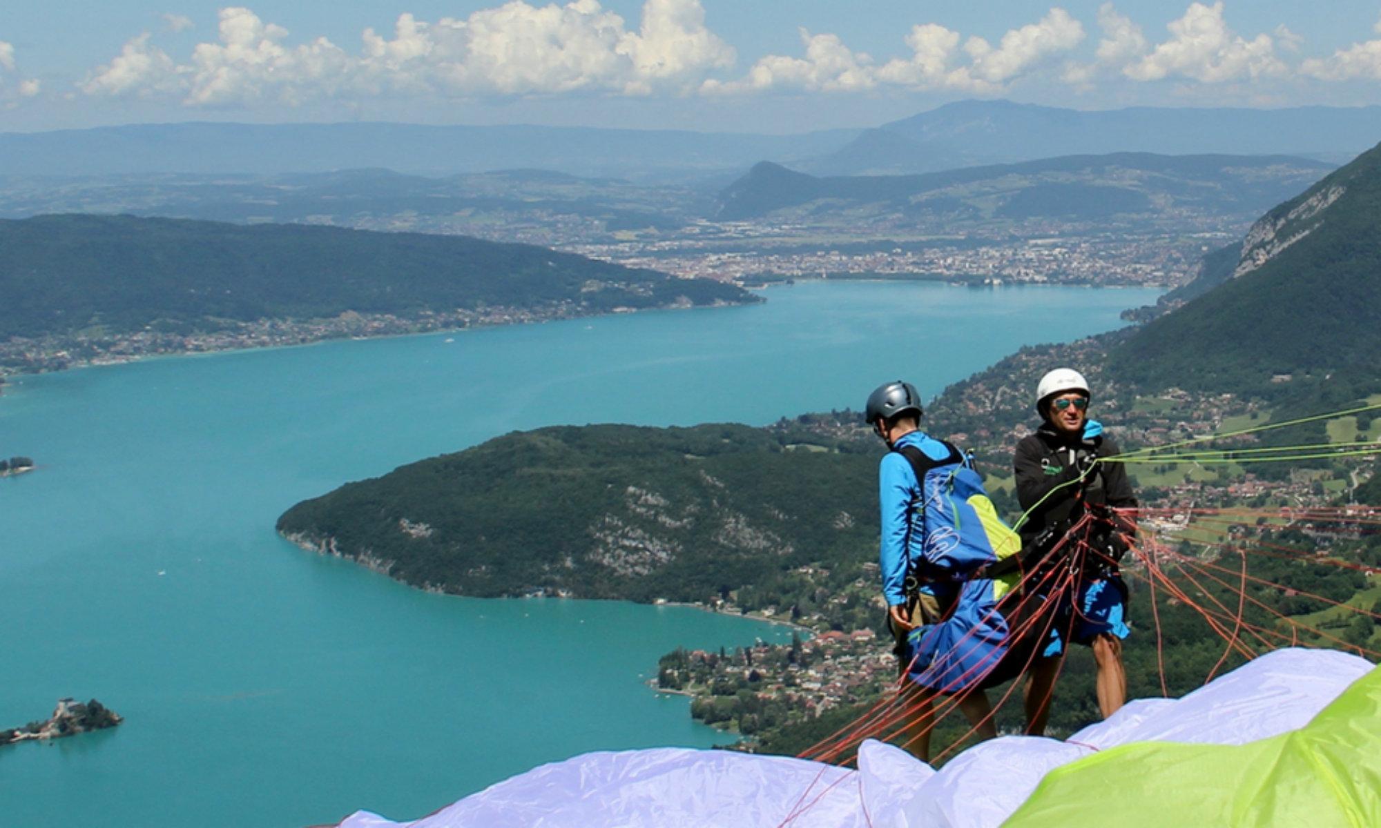 Un parapente tandem s'apprête à décoller au-dessus du lac d'Annecy.