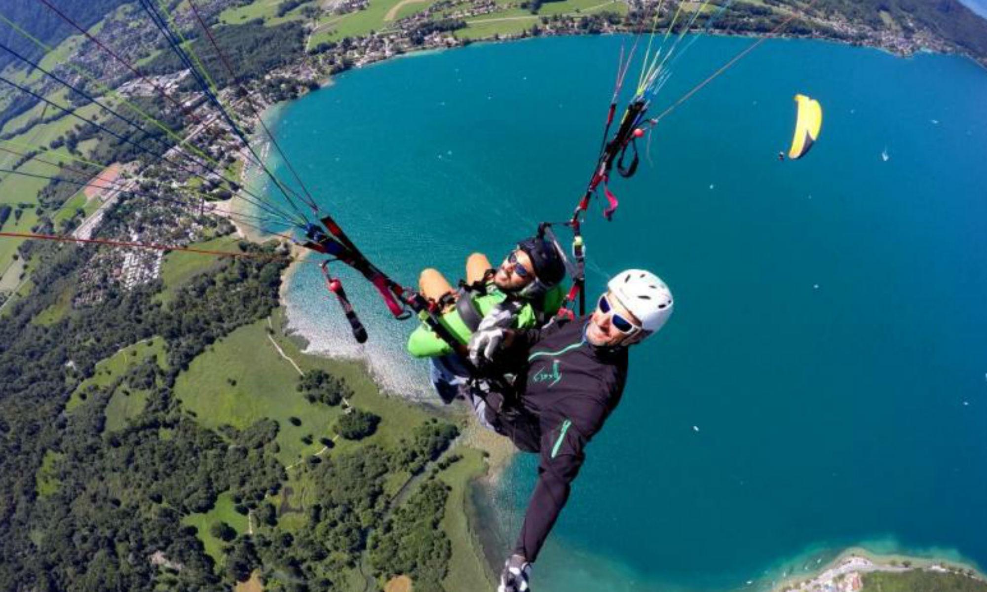 Un jeune homme tout sourire survole le lac d'Annecy en parapente avec un pilote de l'école de parapente Takamaka.