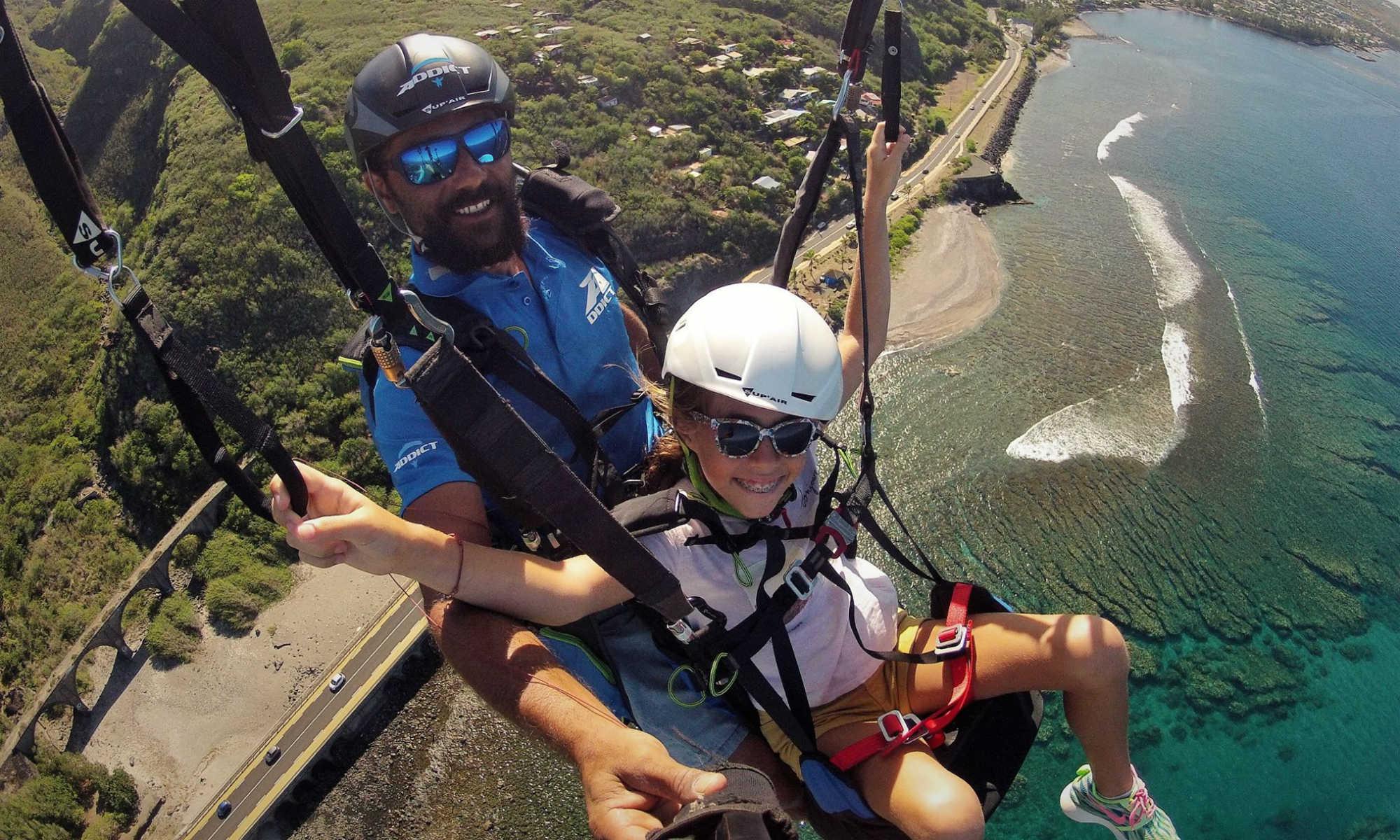 Un enfant souriant prend les commandes lors d'un vol en parapente à La Réunion.