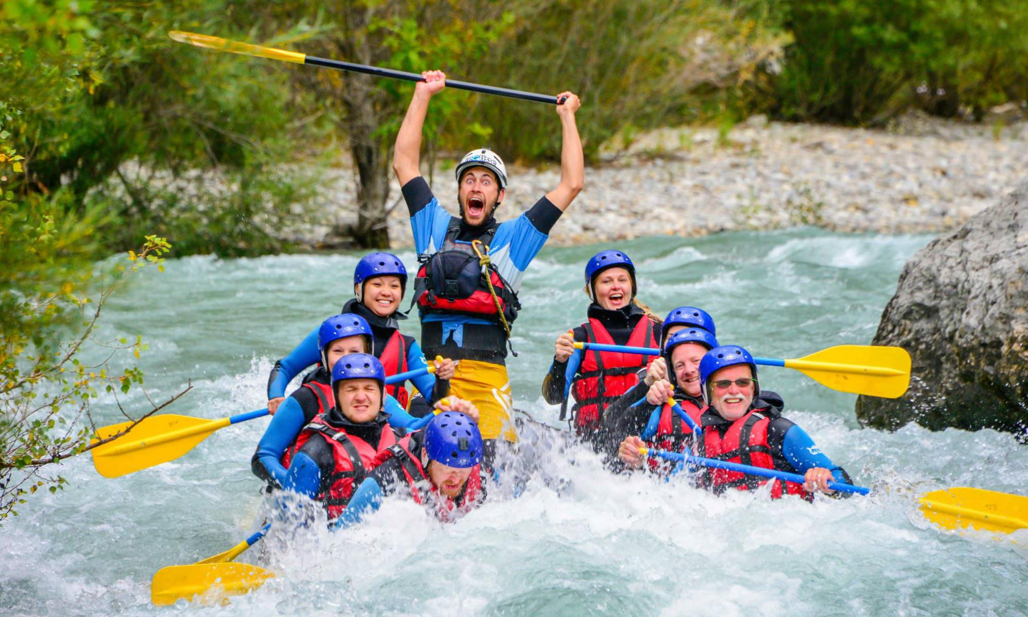 Huit rafteurs traversent un rapide lors d'une activité de rafting sur le Verdon et le guide lève sa pagaie.