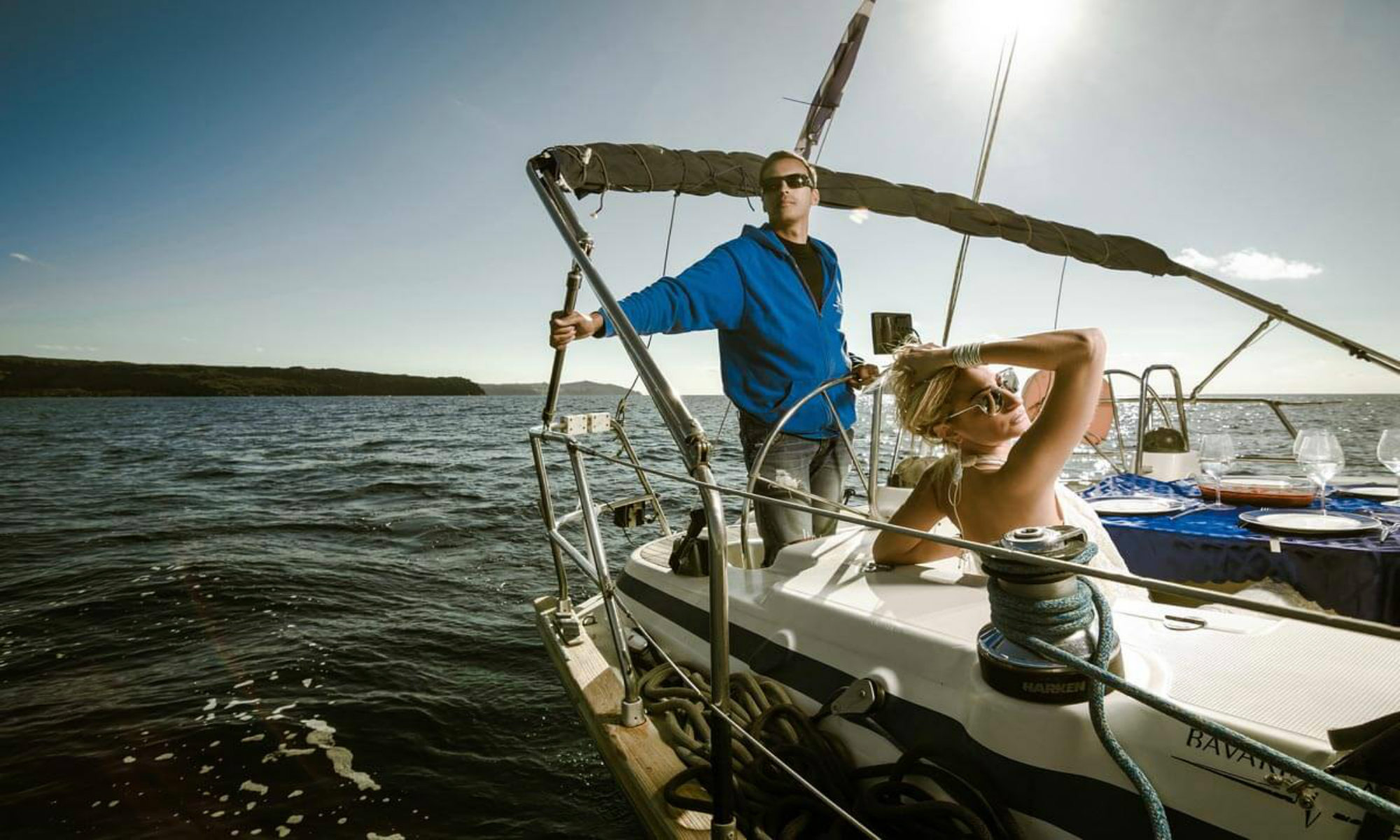 The captain and his female guest are enjoying a boat tour around the island of Santorini.