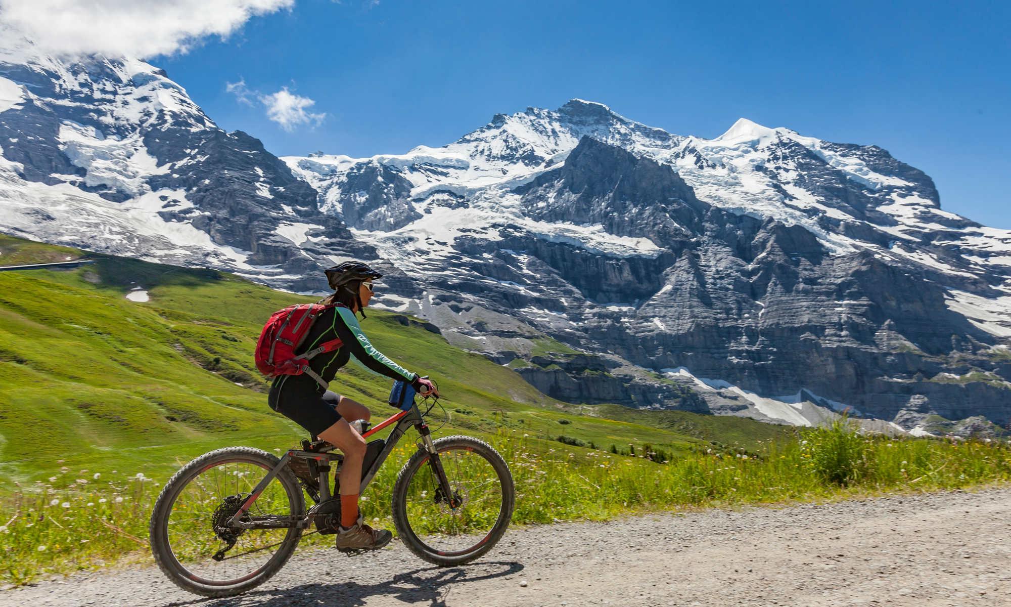 Eine Frau beim Mountainbiken vor einem alpinen Bergpanorama.