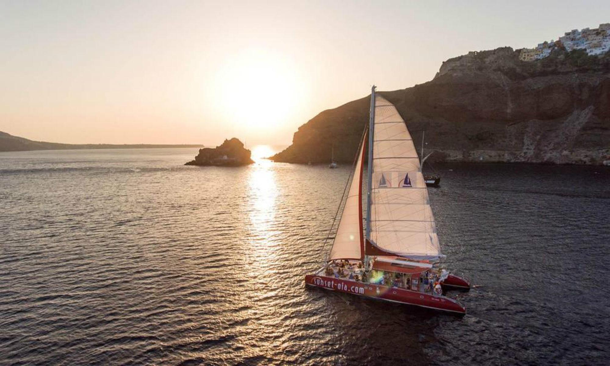 A catamaran sails around the island of Santorini at sunset.
