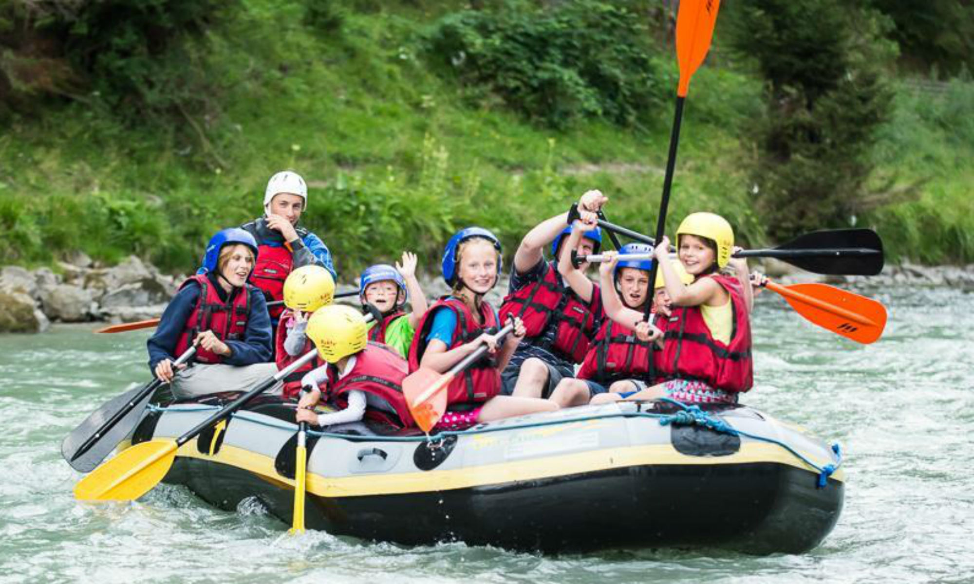A large family group in a rubber dinghy while out rafting on the Saalach River.