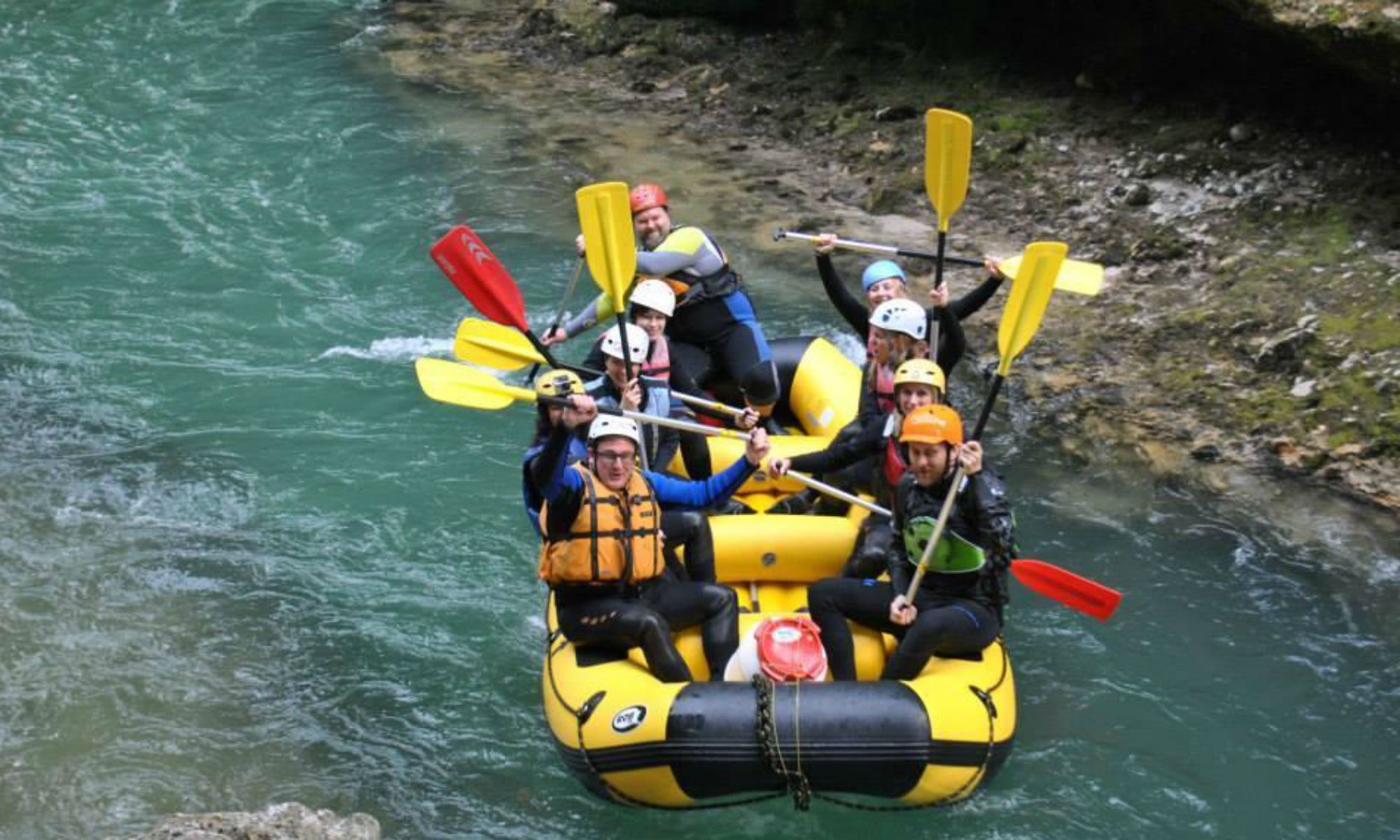 A group of people in a rubber dinghy on the Salza River while out white water rafting in Austria.