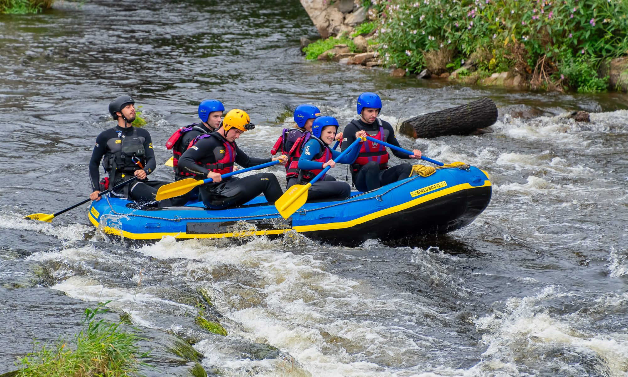 A group of people rafting along the River Dee in Wales.