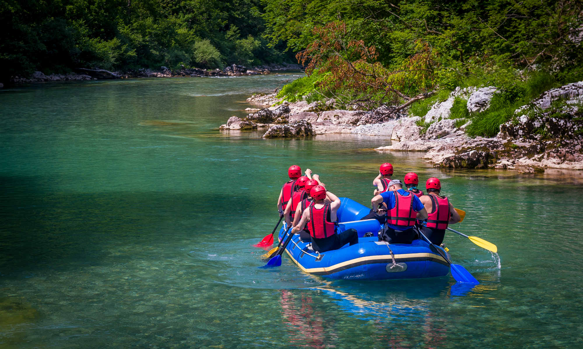 A group of people paddling through the emerald green waters of the Tara River.
