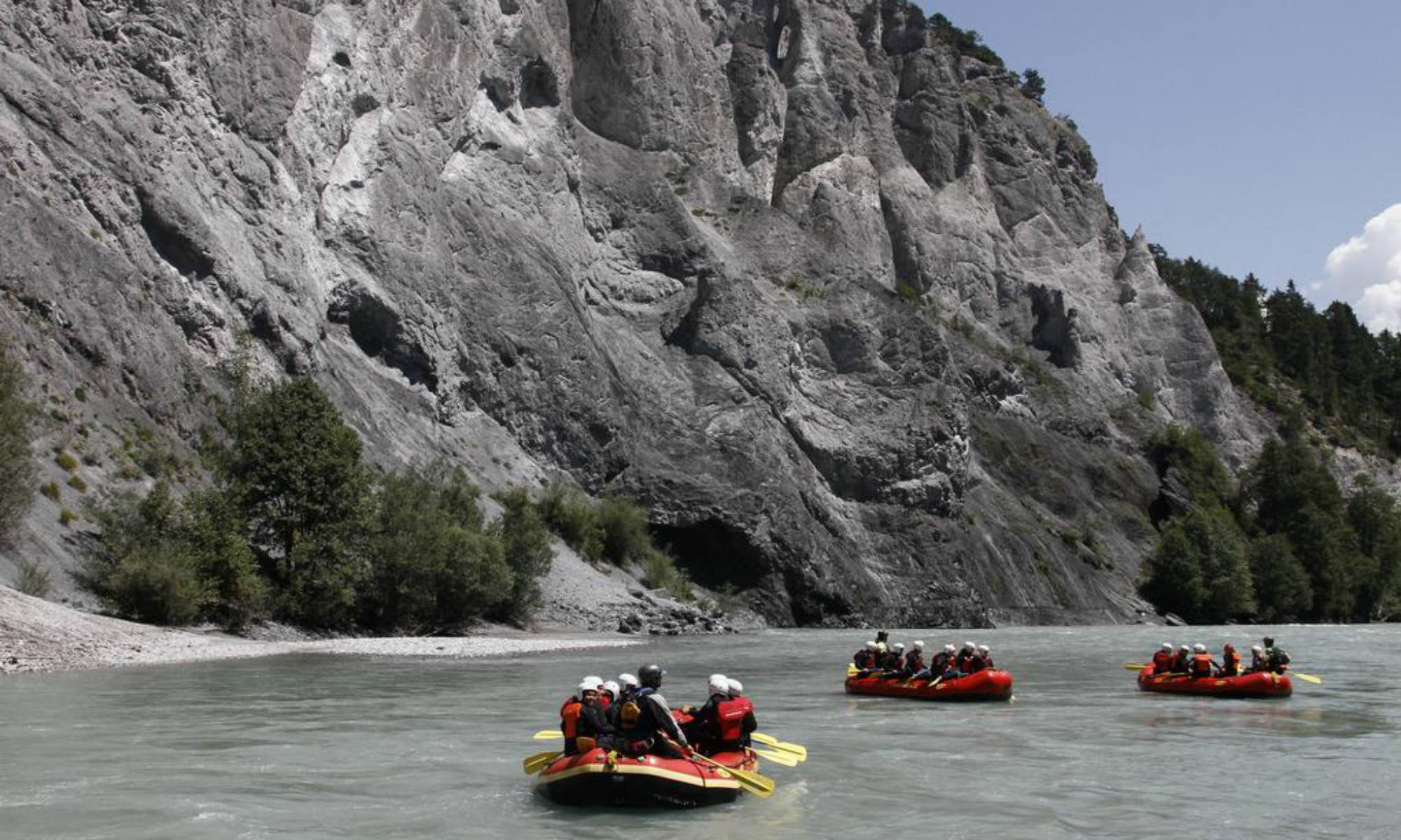 Several groups of people are white water rafting on the Vorderrhein in Switzerland.
